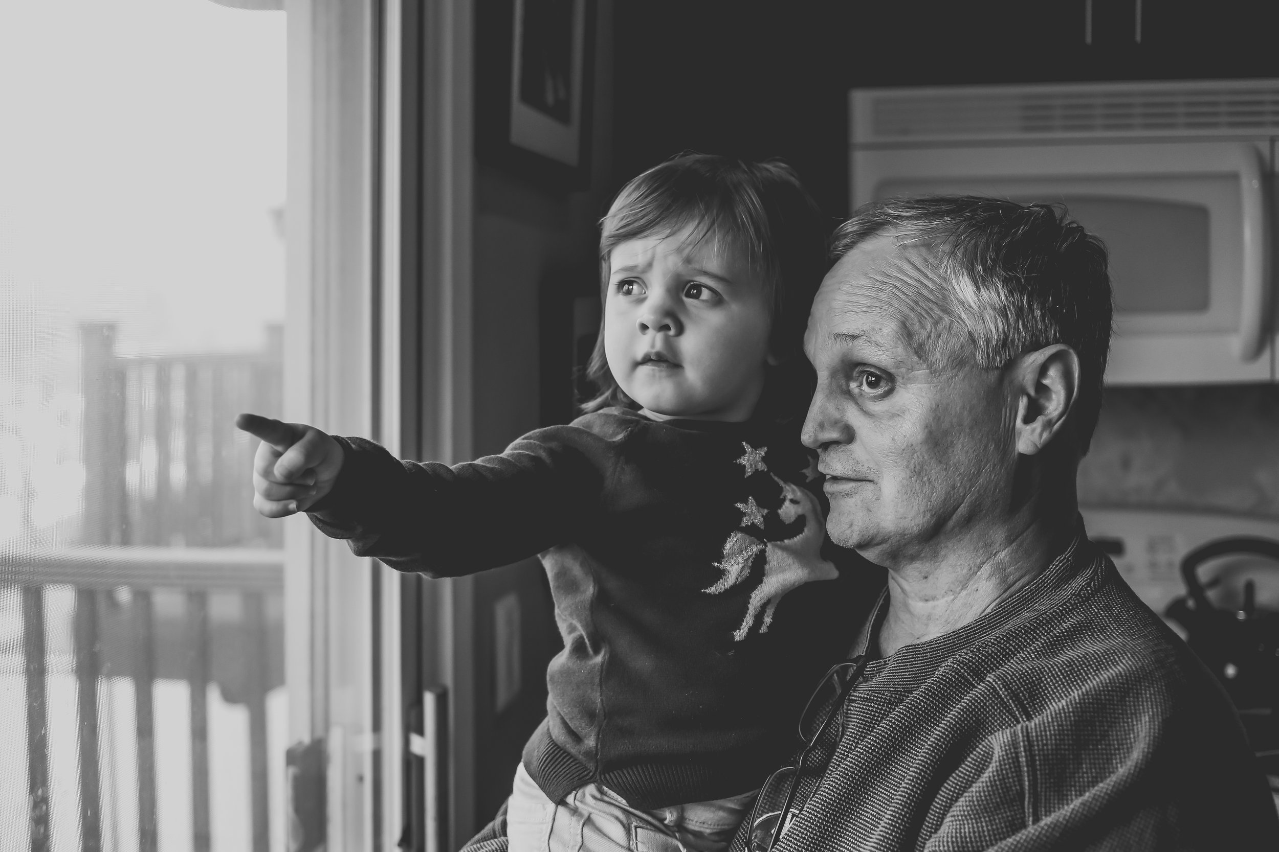 Toddler girl looking out the window with Grandpa, Lehigh Valley documentary family photography session.