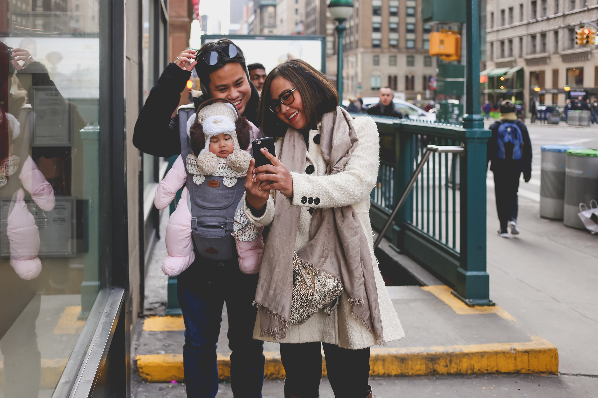 Family taking a selfie while on vacation during a photo session in New York City with Jen Grima, documentary photographer.