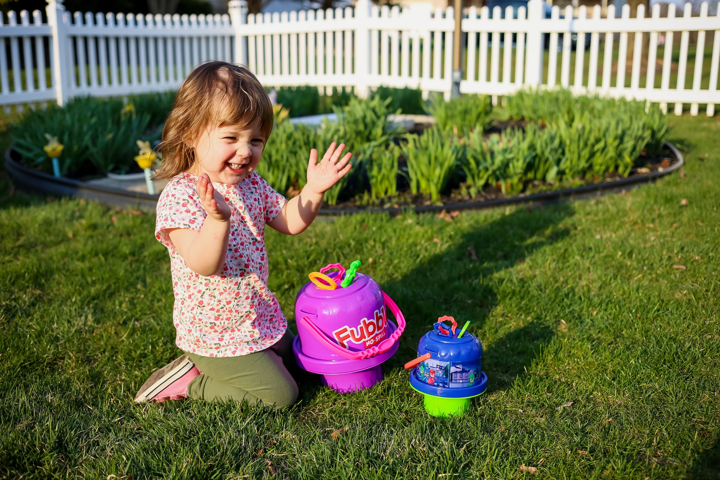 Toddler girl playing with bubbles during a backyard family photo session in Lehigh Valley, Pennsylvania.