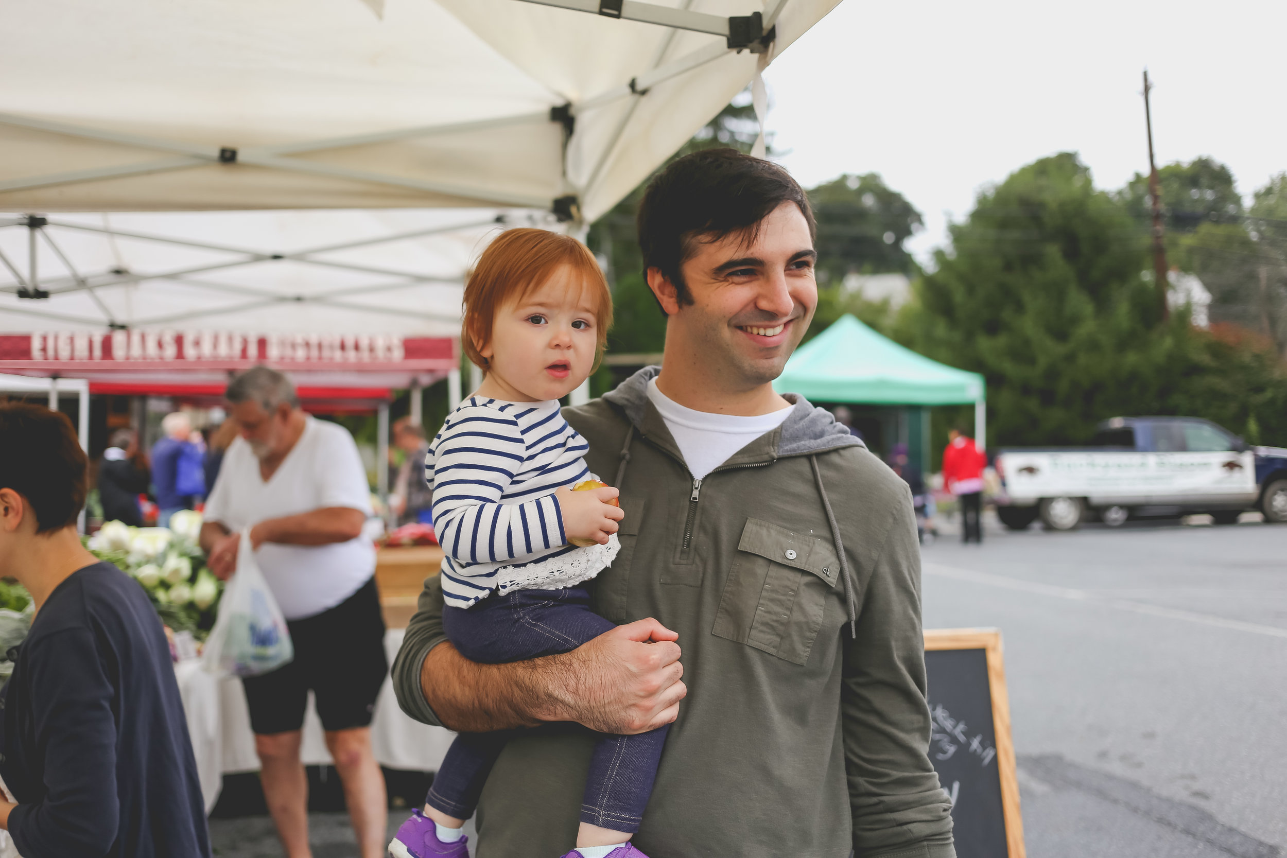 Father holding his baby daughter at the farmer's market in Emmaus, PA.
