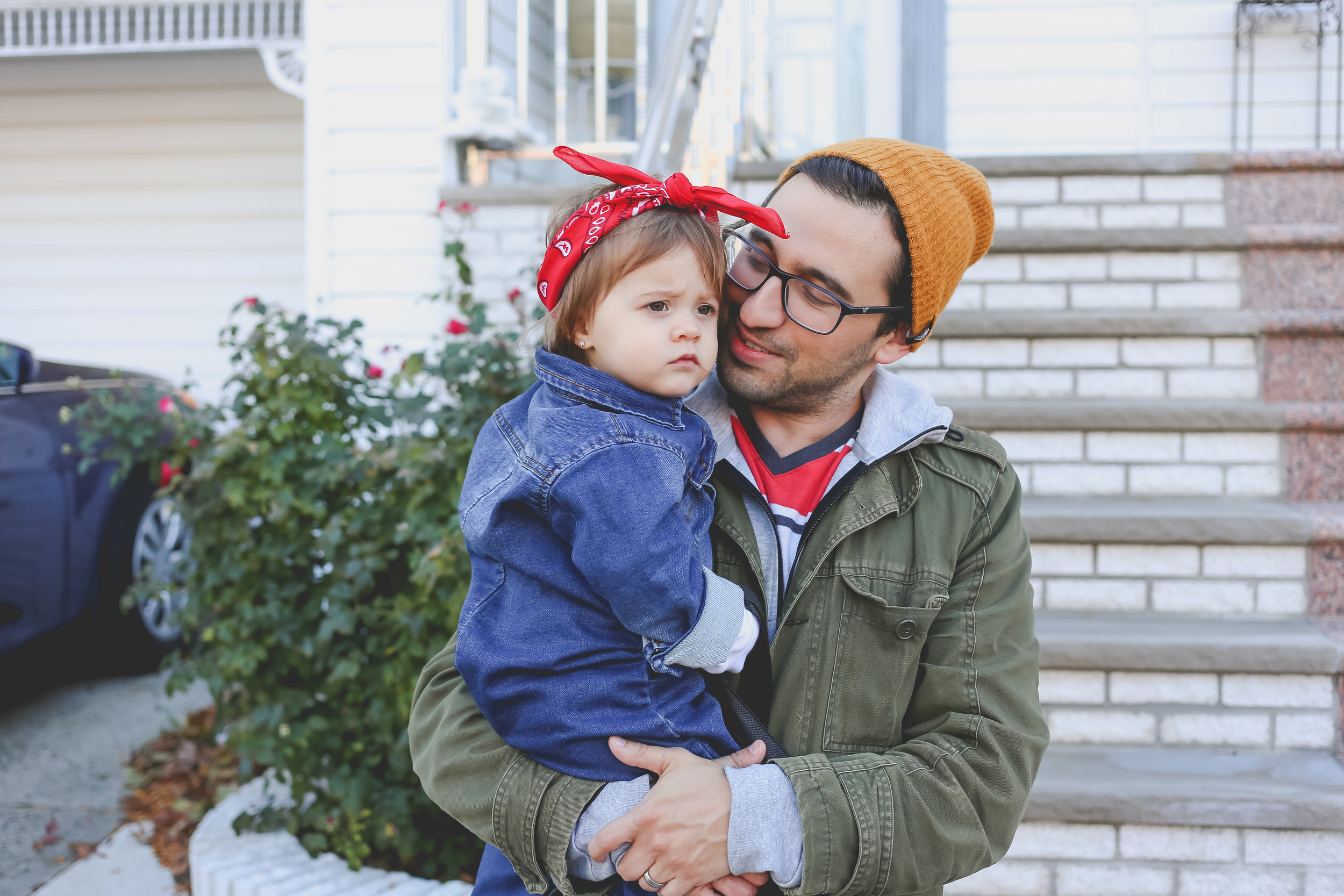 Father with his toddler daughter, dressed as Rosie the Riveter on Halloween.