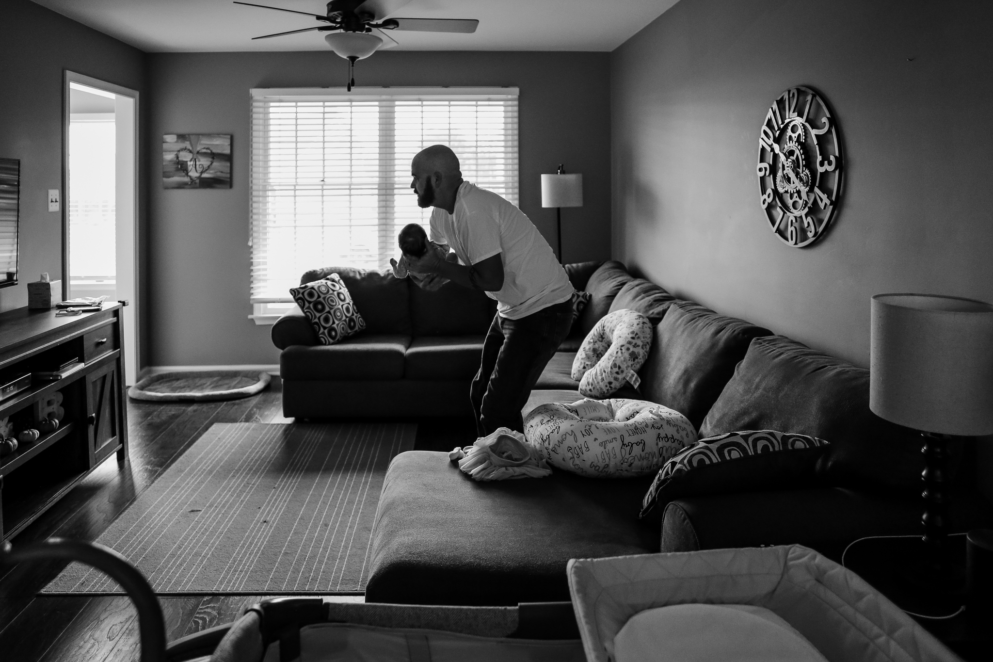 Father picking up his infant daughter during an at home family photography session in Lehigh Valley, Pennsylvania.