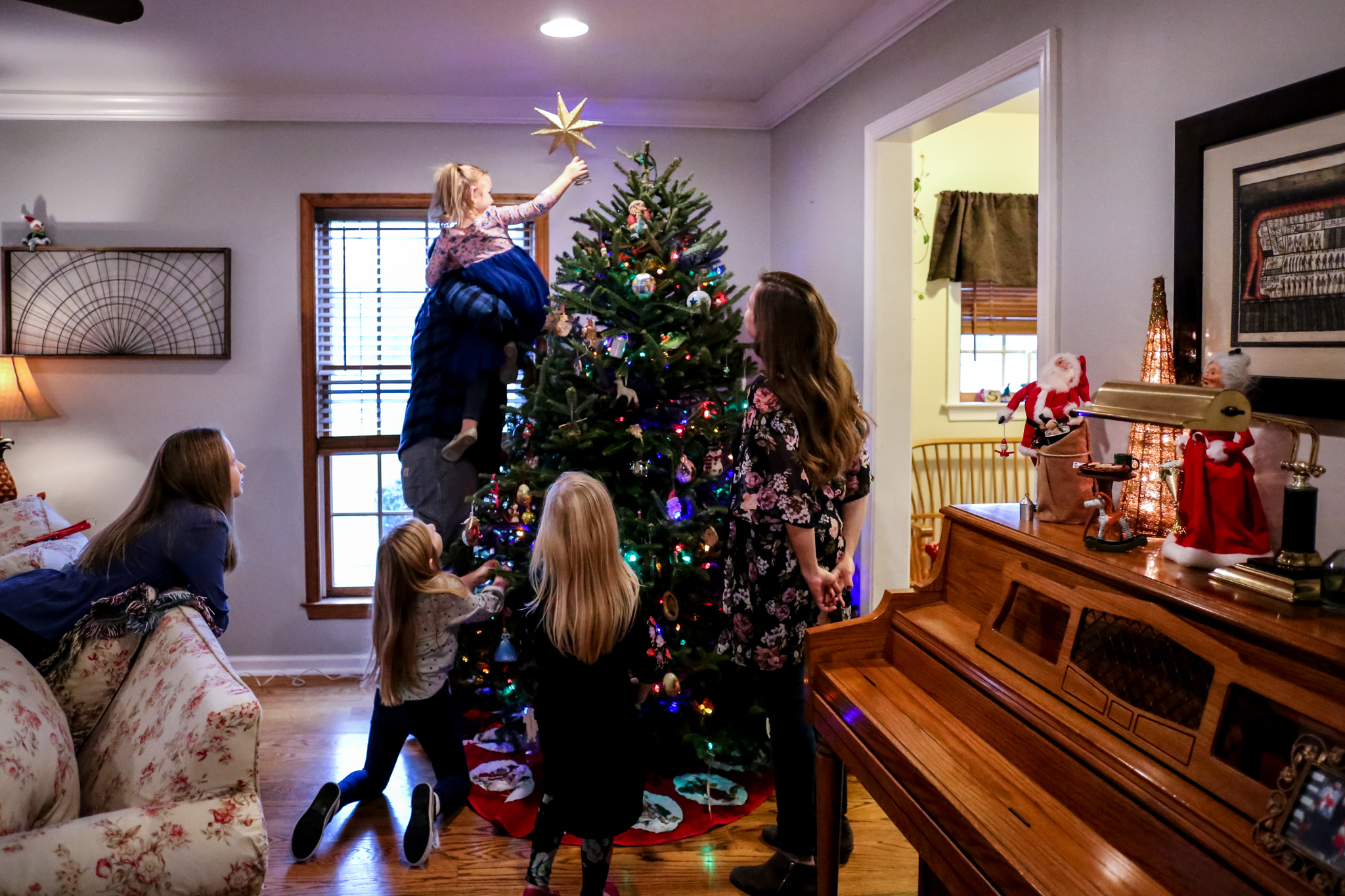 Young girl puts the star on top of the Christmas tree during an at-home holiday family photo session in Lehigh Valley, PA.