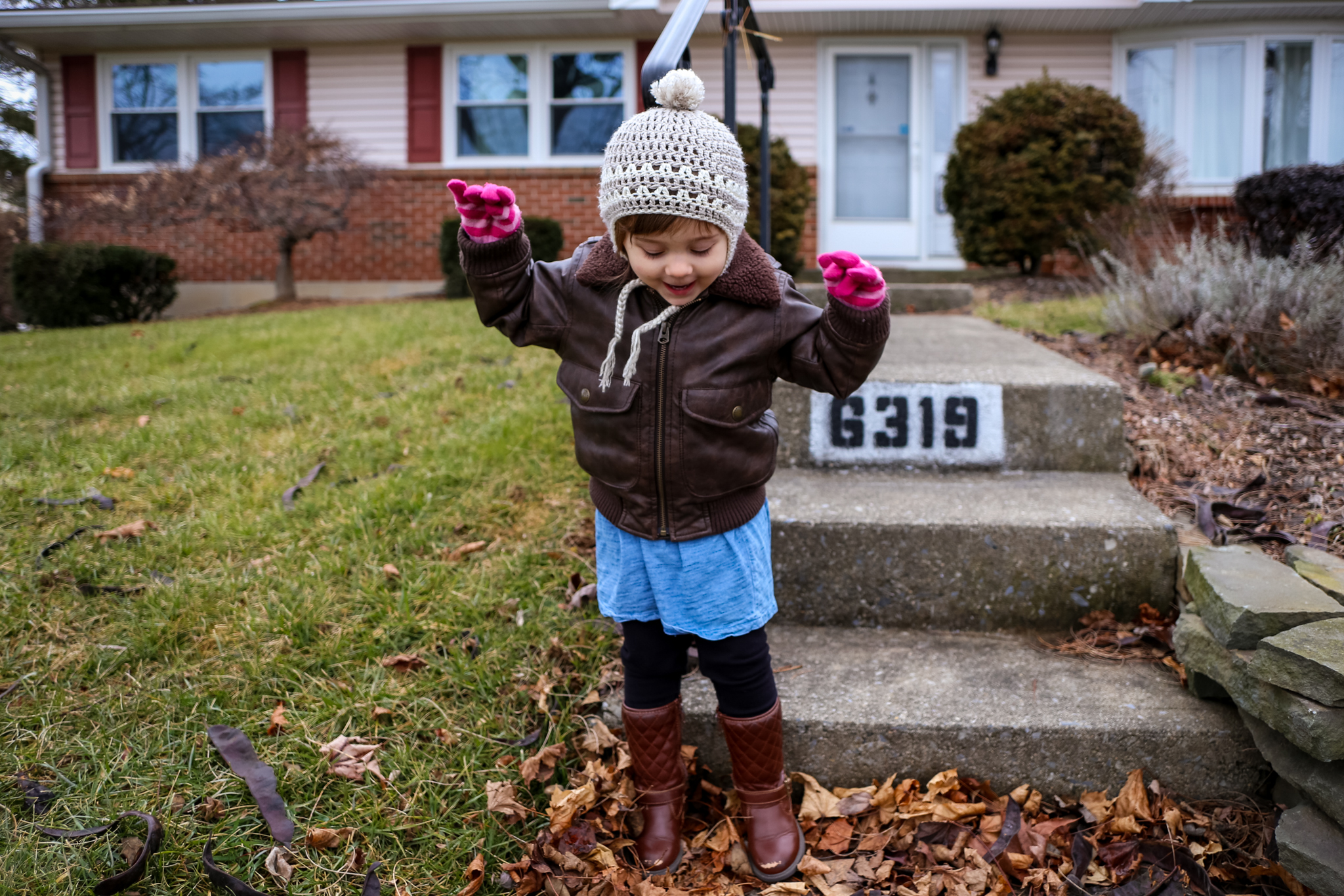 Toddler in her winter coat and hat, outside her home during a family photography session in Macungie, PA.