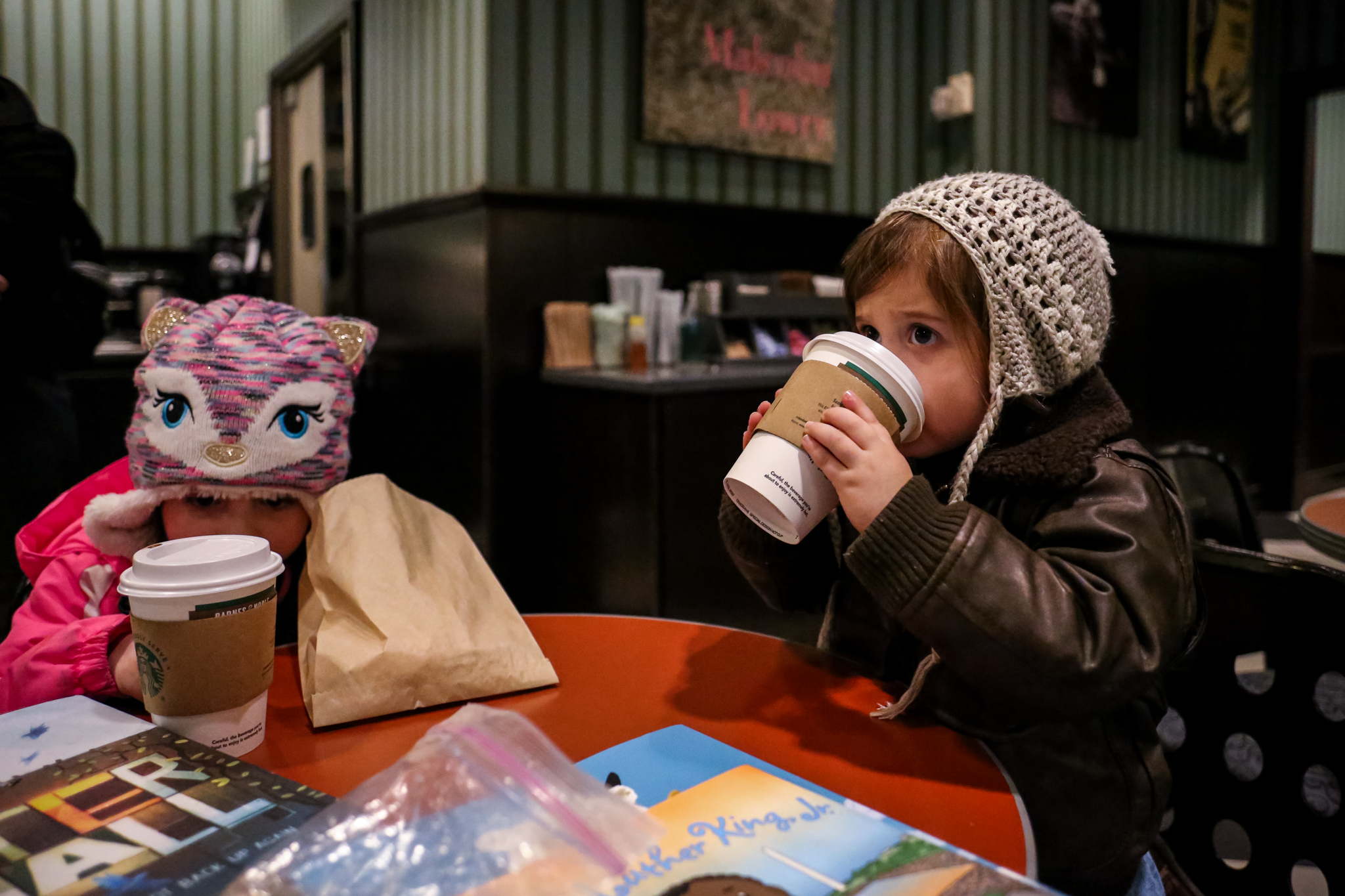 Little girl warming up with some hot chocolate at Starbucks during her day in the life family photography session to celebrate her third birthday.