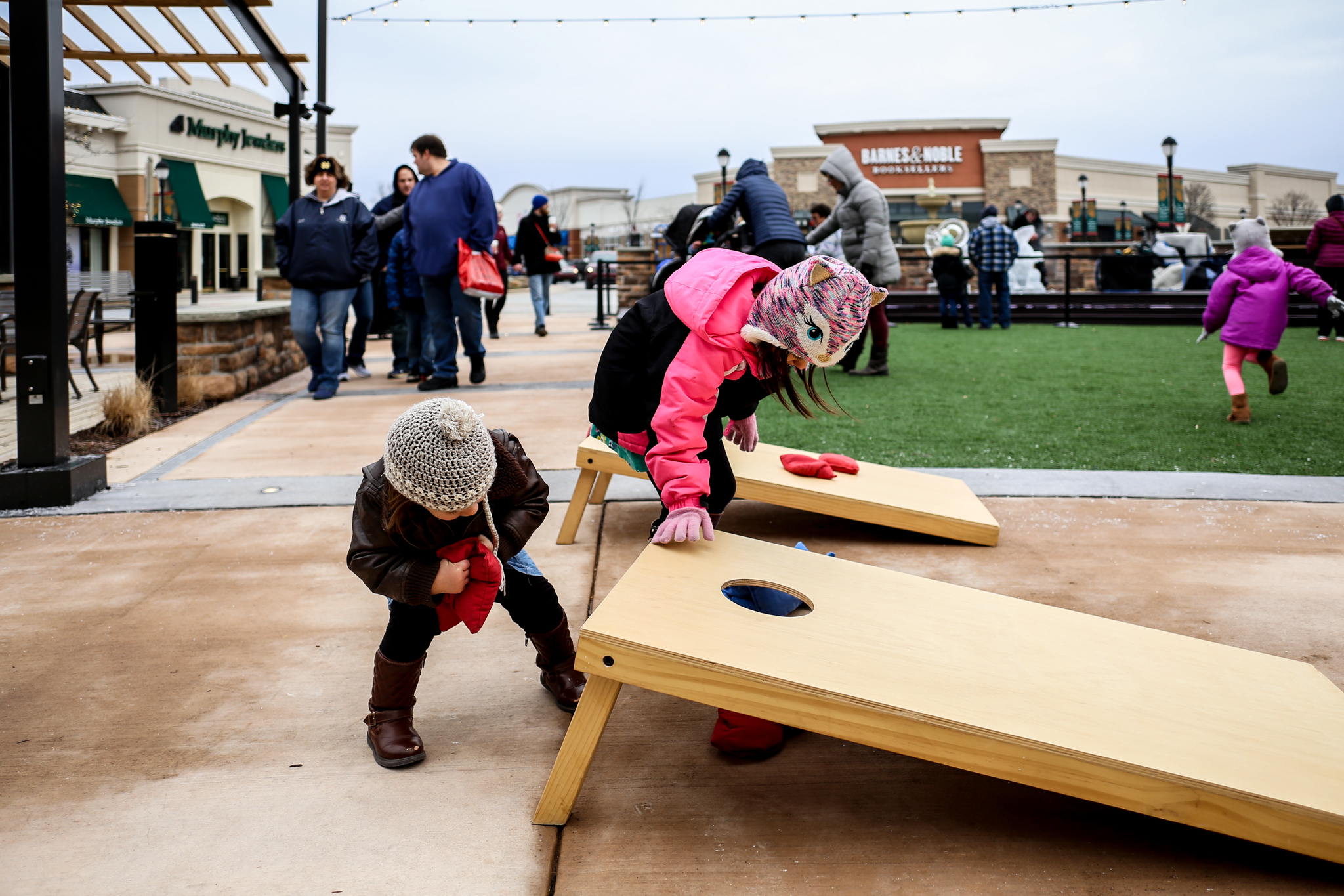 Little girls playing cornhole during the fire and ice festival at The Shops at Saucon Valley in Lehigh Valley, PA.