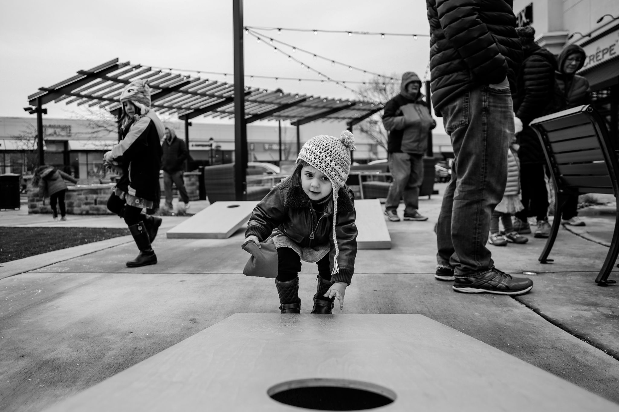 Little girl enjoying a game of cornhole during her family photography session at The Promenade Shops at Saucon Valley in Lehigh Valley, PA.