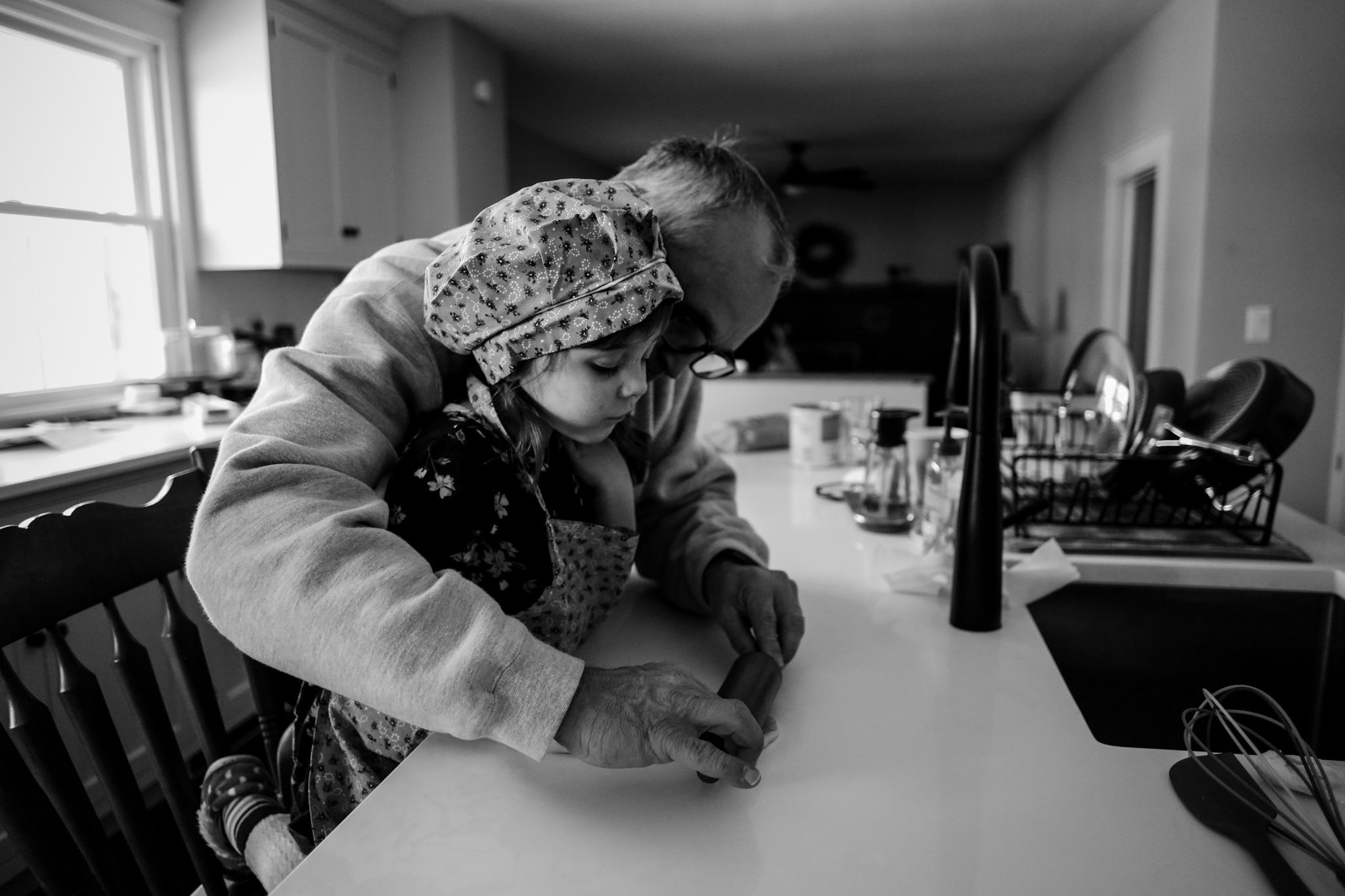 Young girl getting some help from grandpa while baking during an in home photo session with Jen Grima, Lehigh Valley family photographer.