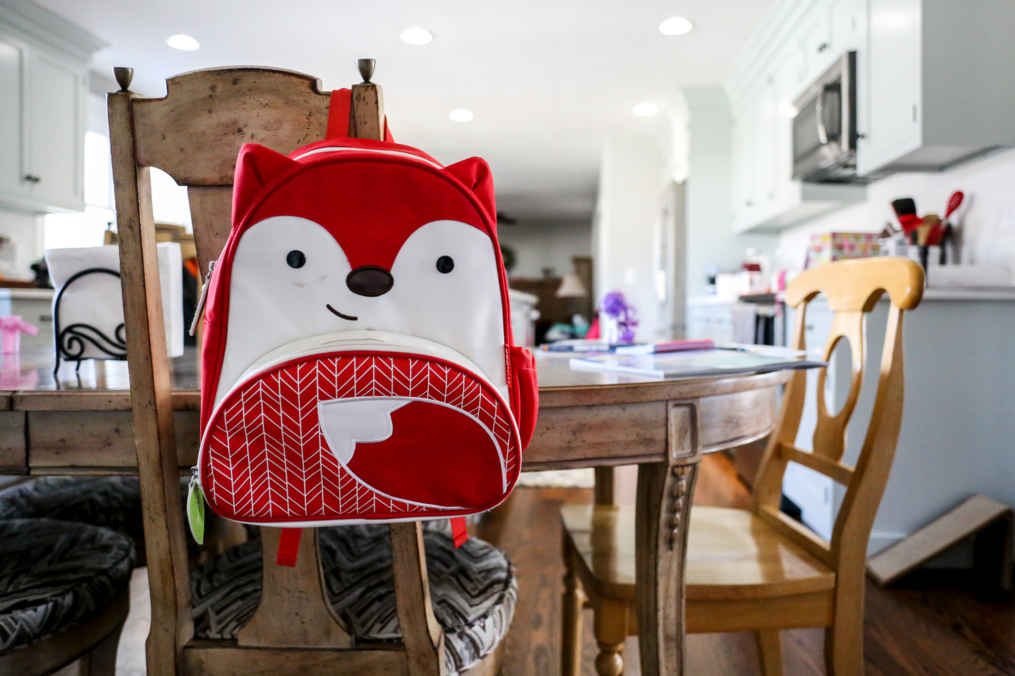 Little kid's backpack on the back of a dining room chair, taken during an at home family photo session in Macungie, PA.