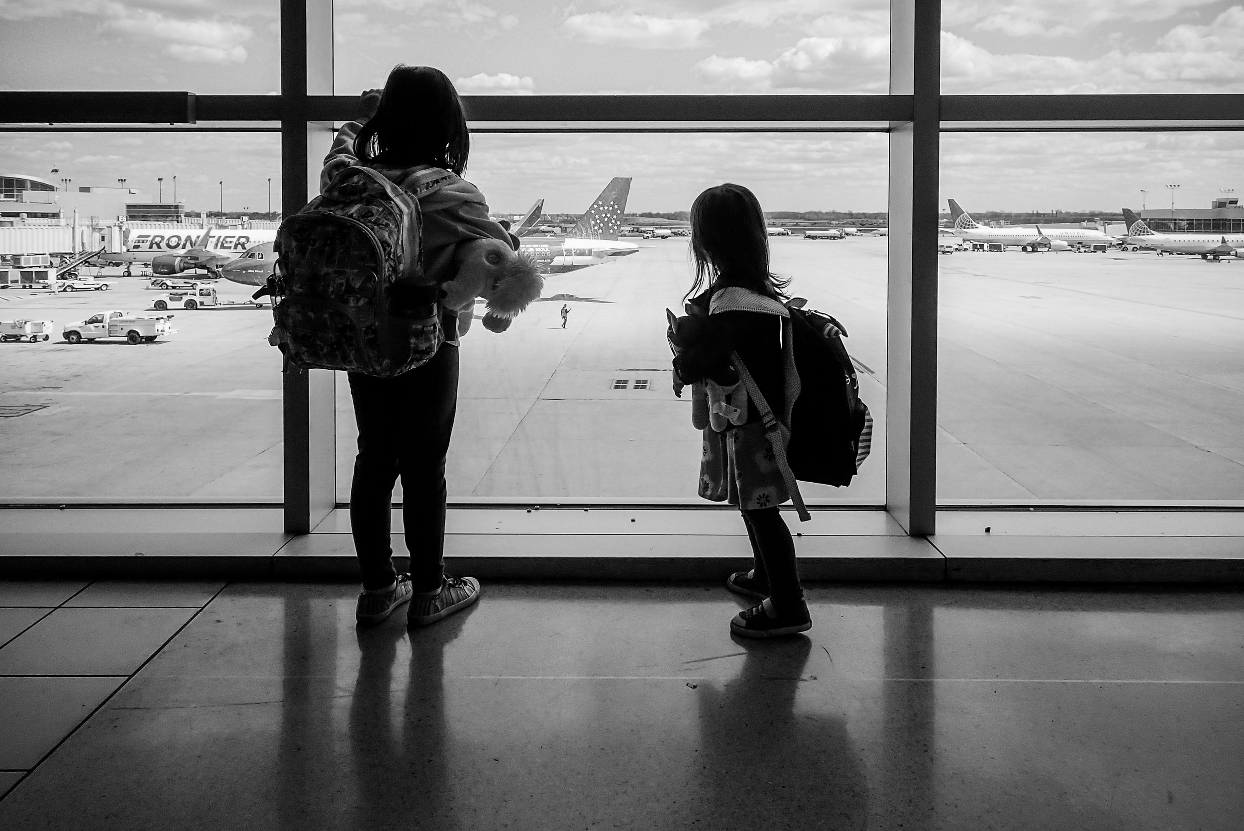 Young girls looking out the window while waiting for their flight at Philadelphia International Airport.