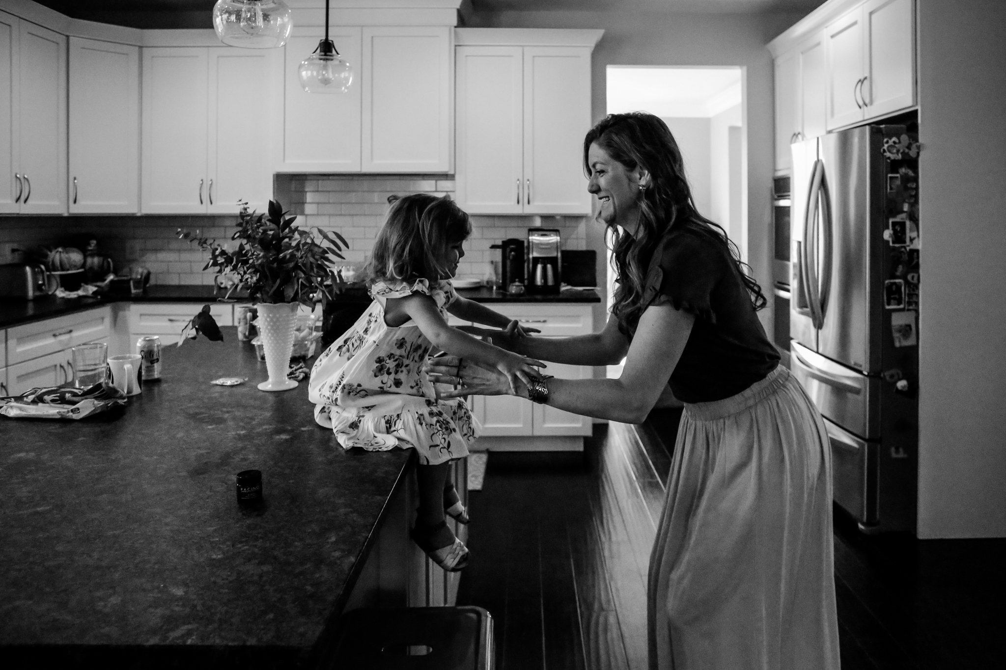 Daughter jumping off the counter into her mother's arms in the kitchen at their home in Coopersburg, PA.