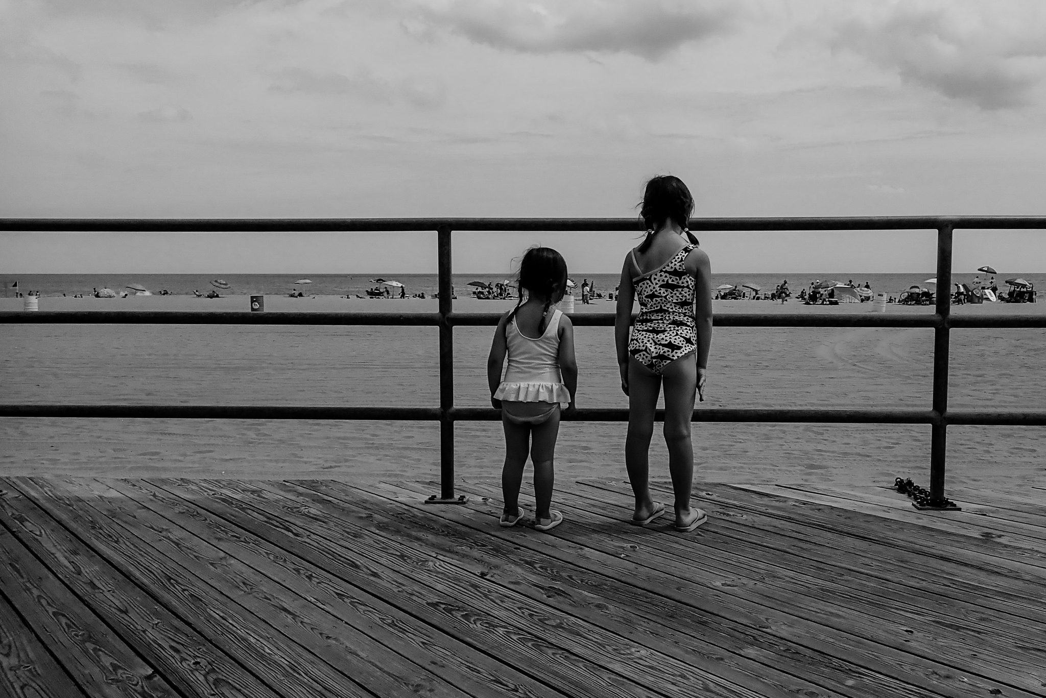 Two girls look out onto the beach from the boardwalk at the jersey shore.