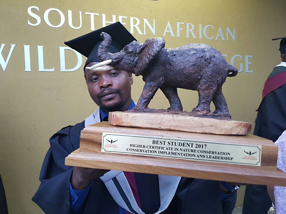 Zambian student George Phiri poses with one of several top student honors he earnedfrom his ZCP sponsorship to the Southern African Wildlife College.