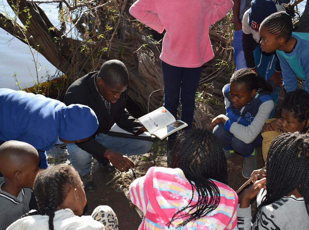 ZCP Researcher and Educator Lameck Sakala, a graduate of ZCP collaborative Conservation Club programmes himself, conducts a tracking exercise with students in Kafue.
