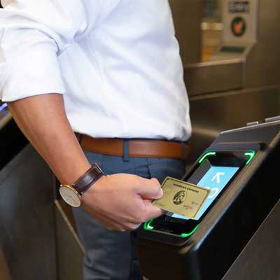 A consumer taps an AmEx card against a subway turnstile to pay a fare. (Image credit: American Express)