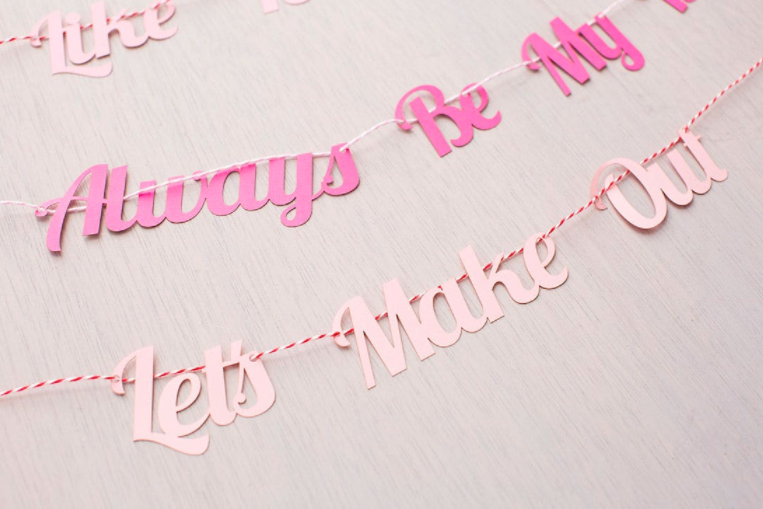 love statement garlands - Source: Brit +CoSimilar to the glitter photo props, create a unique love message for a garland backdrop! Pick your favourite Valentine's Day message, and craft it to this garland to have huge visual impact to your next photoshoot.