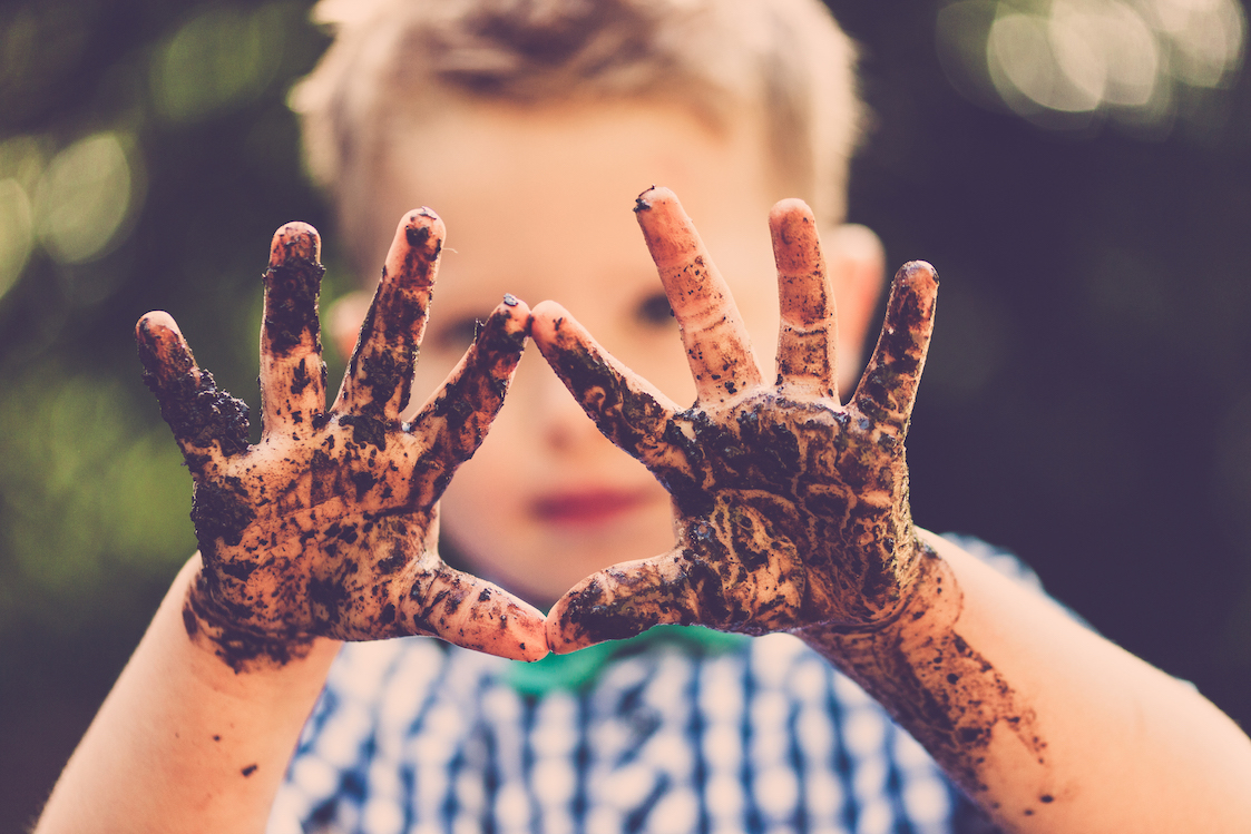 Little boy with muddy hands posing during Shropshire lifestyle photography session
