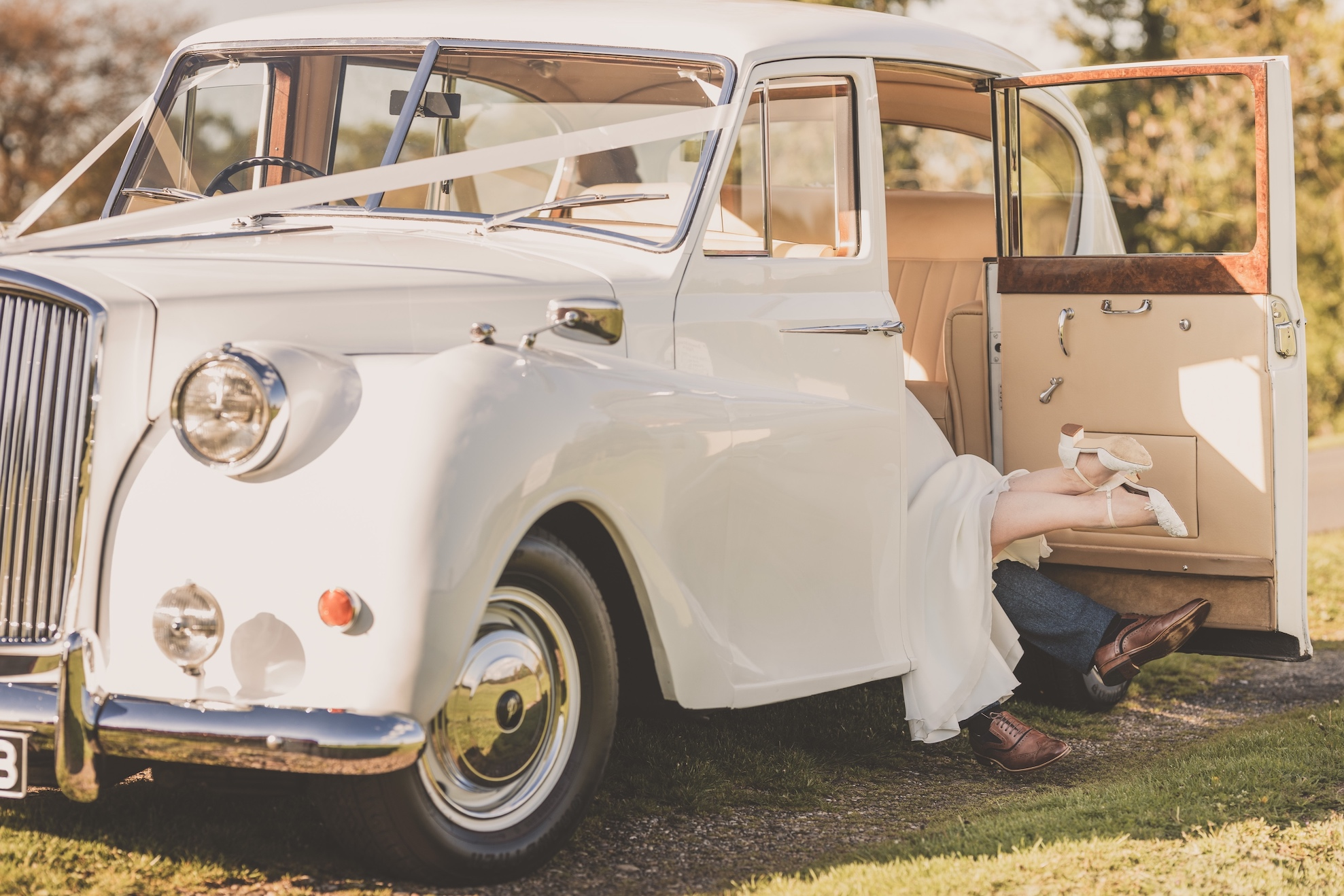 Bride and groom's feet sticking out of a wedding car at Somerford Hall