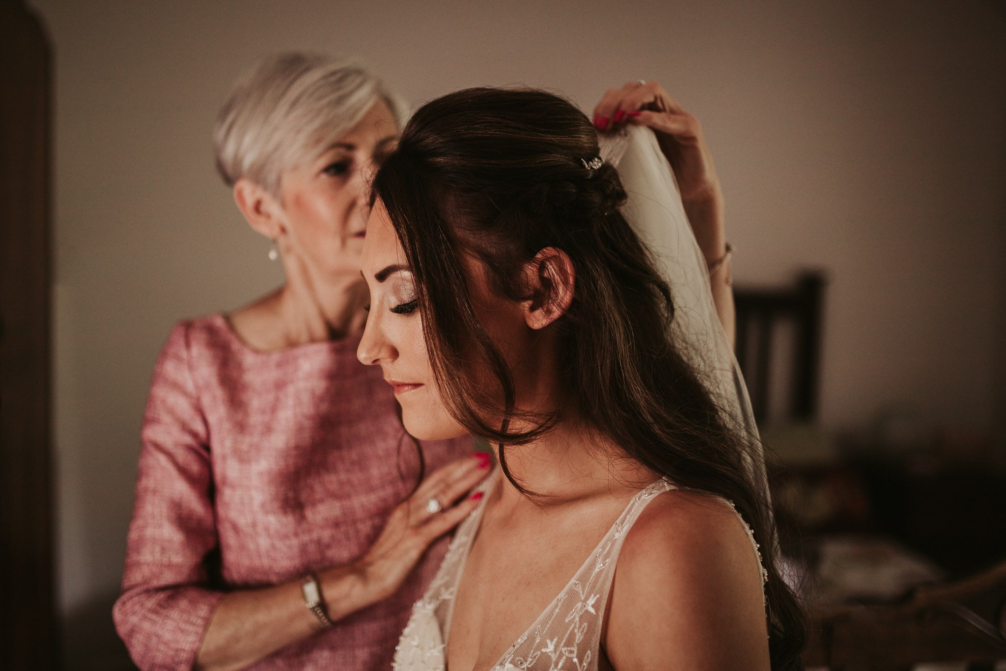 Candid photo of a mother fixing her daughter's veil before her Shropshire wedding at Blists Hill, Ironbridge