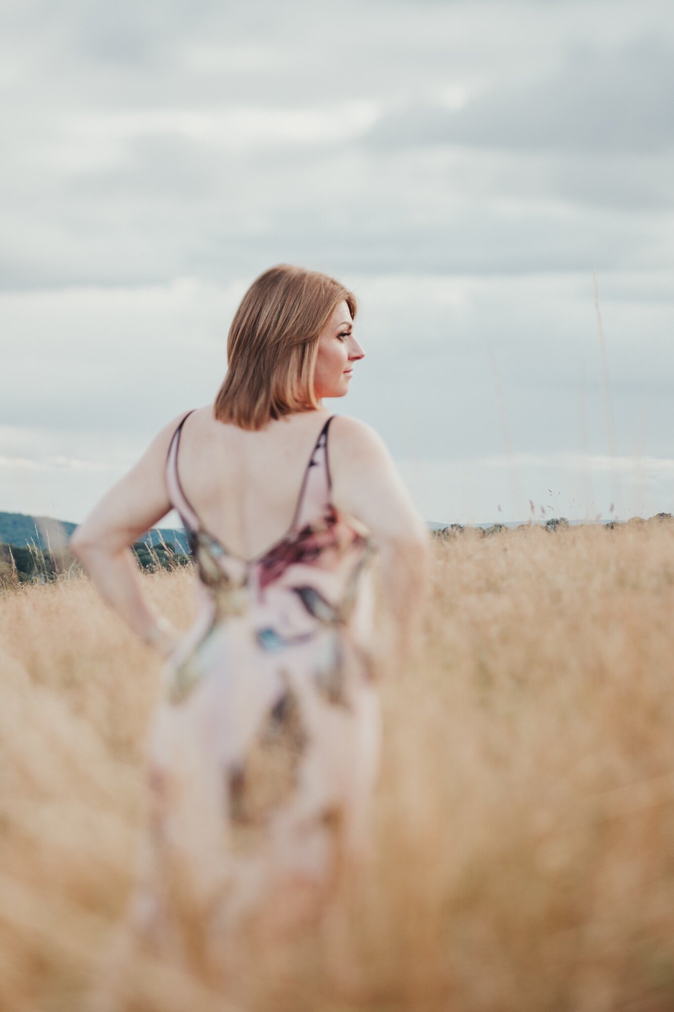 Woman posing in a field during an outdoor boudoir photo shoot in Shropshire
