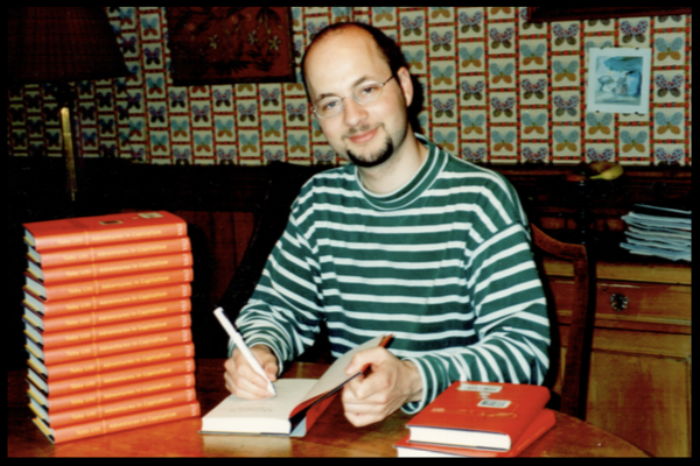 FIGURE 1. At the oval, pine dining table, signing copies of my first book for family and friends. Photo taken at my father's insistence; smug expression, entirely down to me.