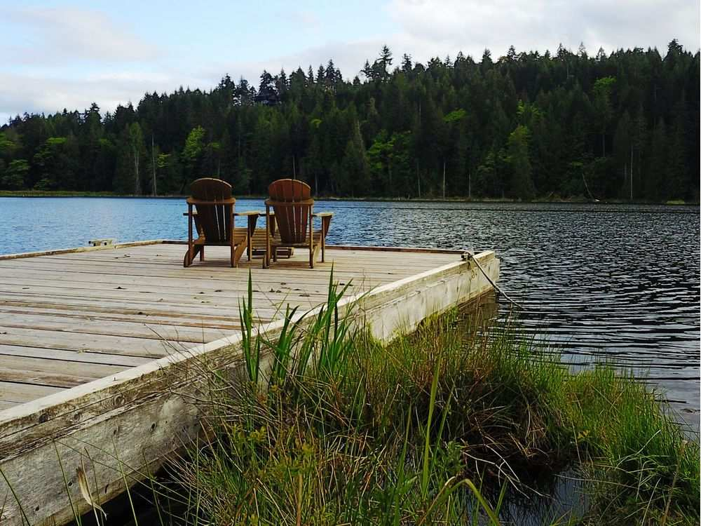 A pair of Adirondack chairs await visitors on the visitors and owners on the dock on secluded Bullock Lake.