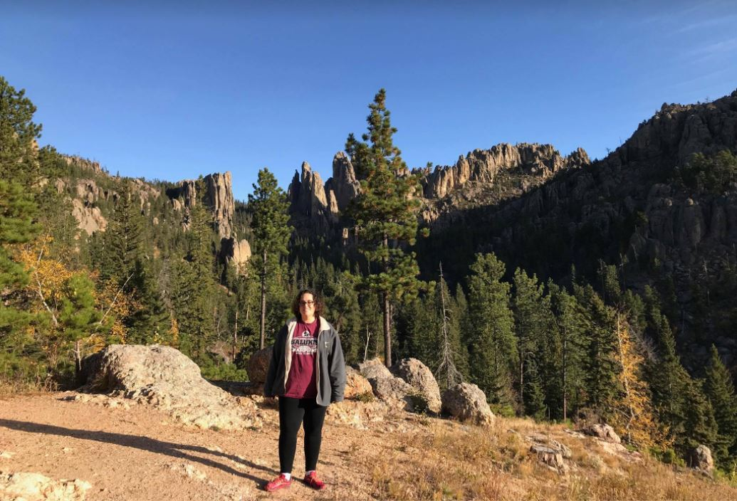 It was a good vacation, to be fair.  Discription: Photo is off a woman wearing black stretch pants, running shoes and a sweatshirt standing on a hill with rocks, evergreens, stone spires and a cloudless blue sky behind her.