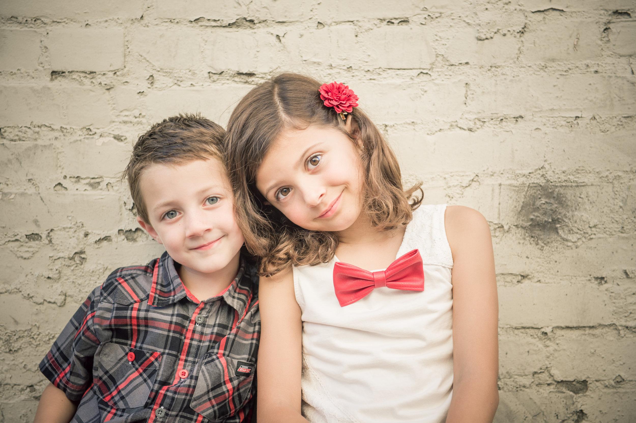 A boy and girl siblings sitting shoulder to shoulder