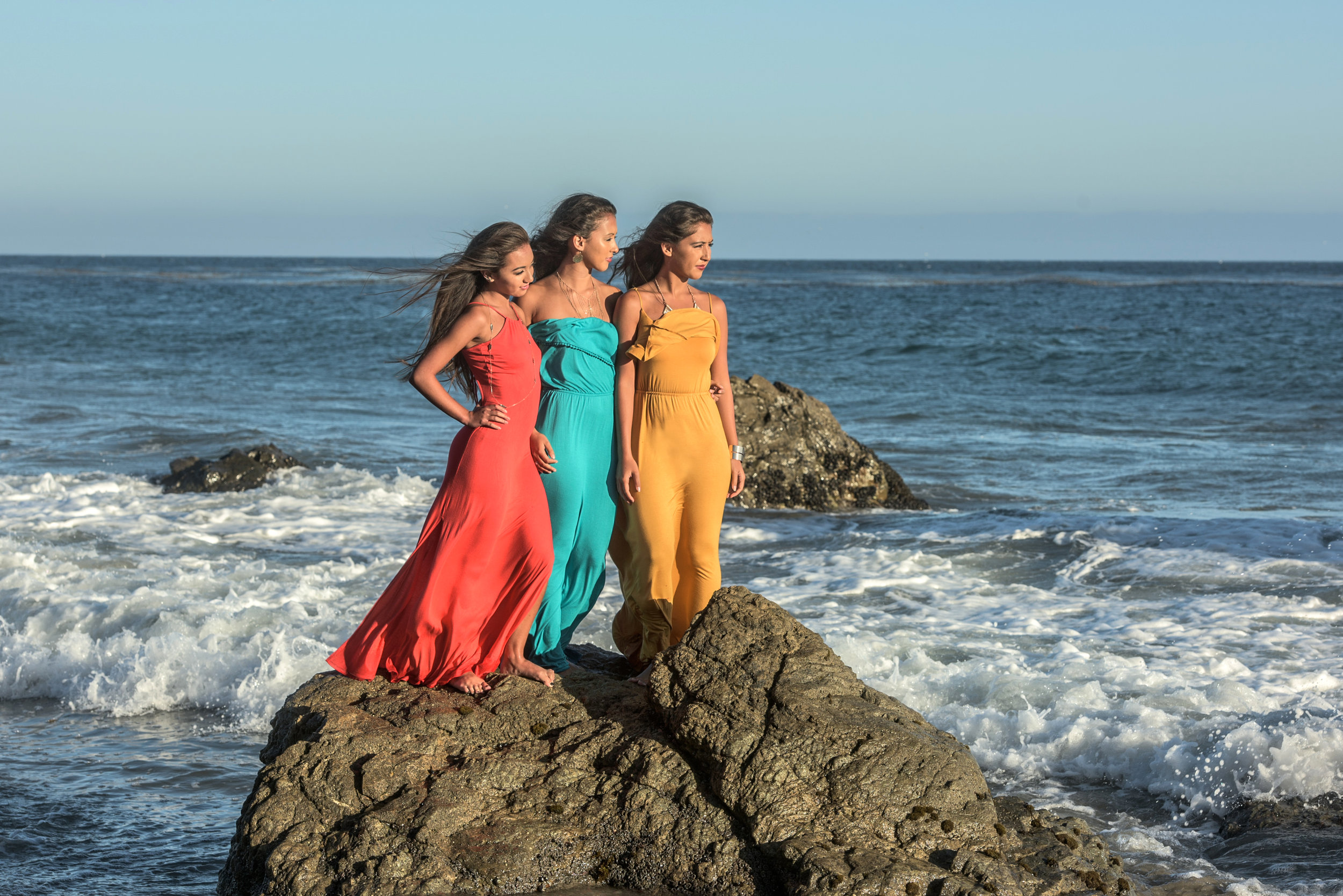 Three sister standing on a rock at the beach