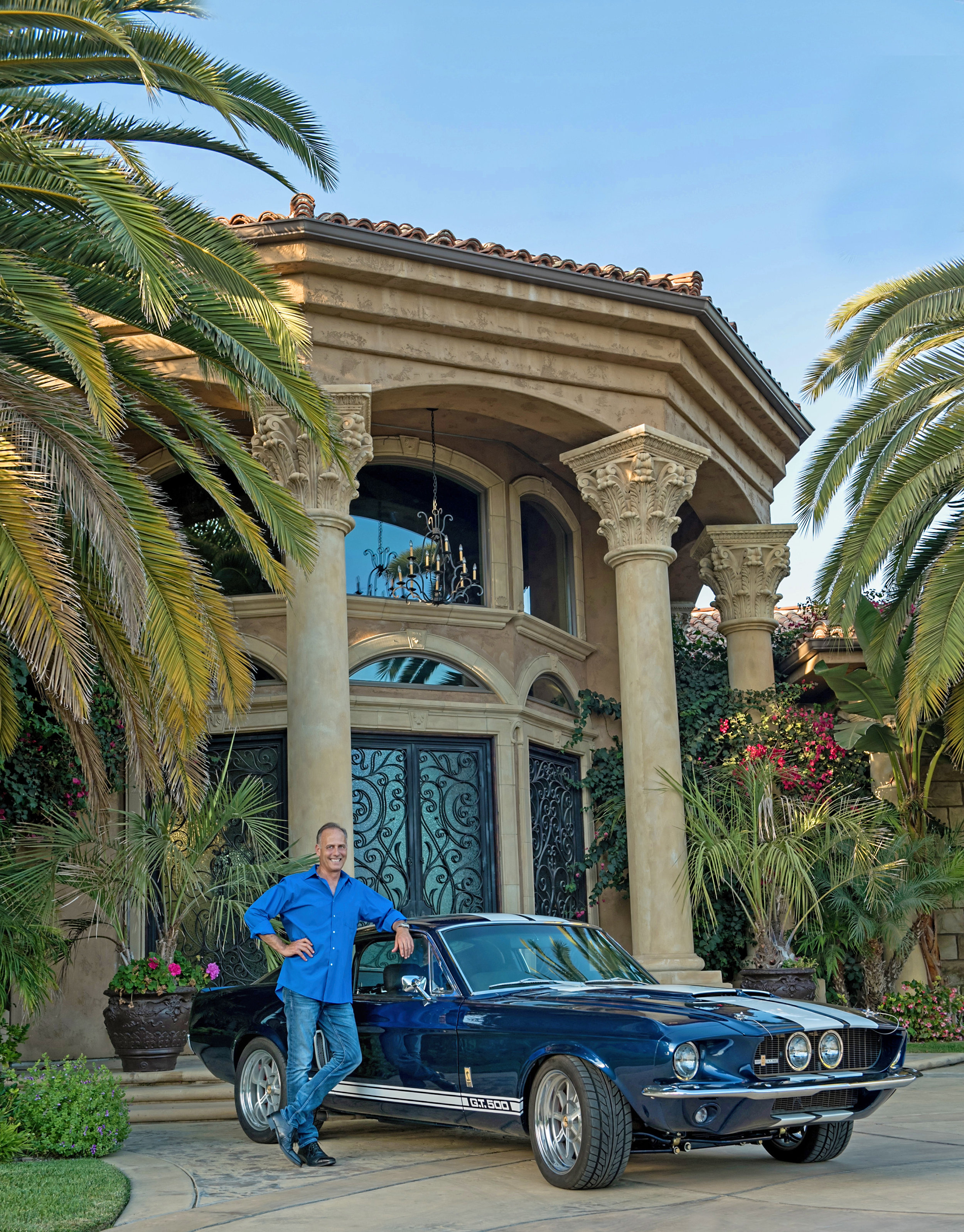 Smiling man standing in front of his home leaning against his car