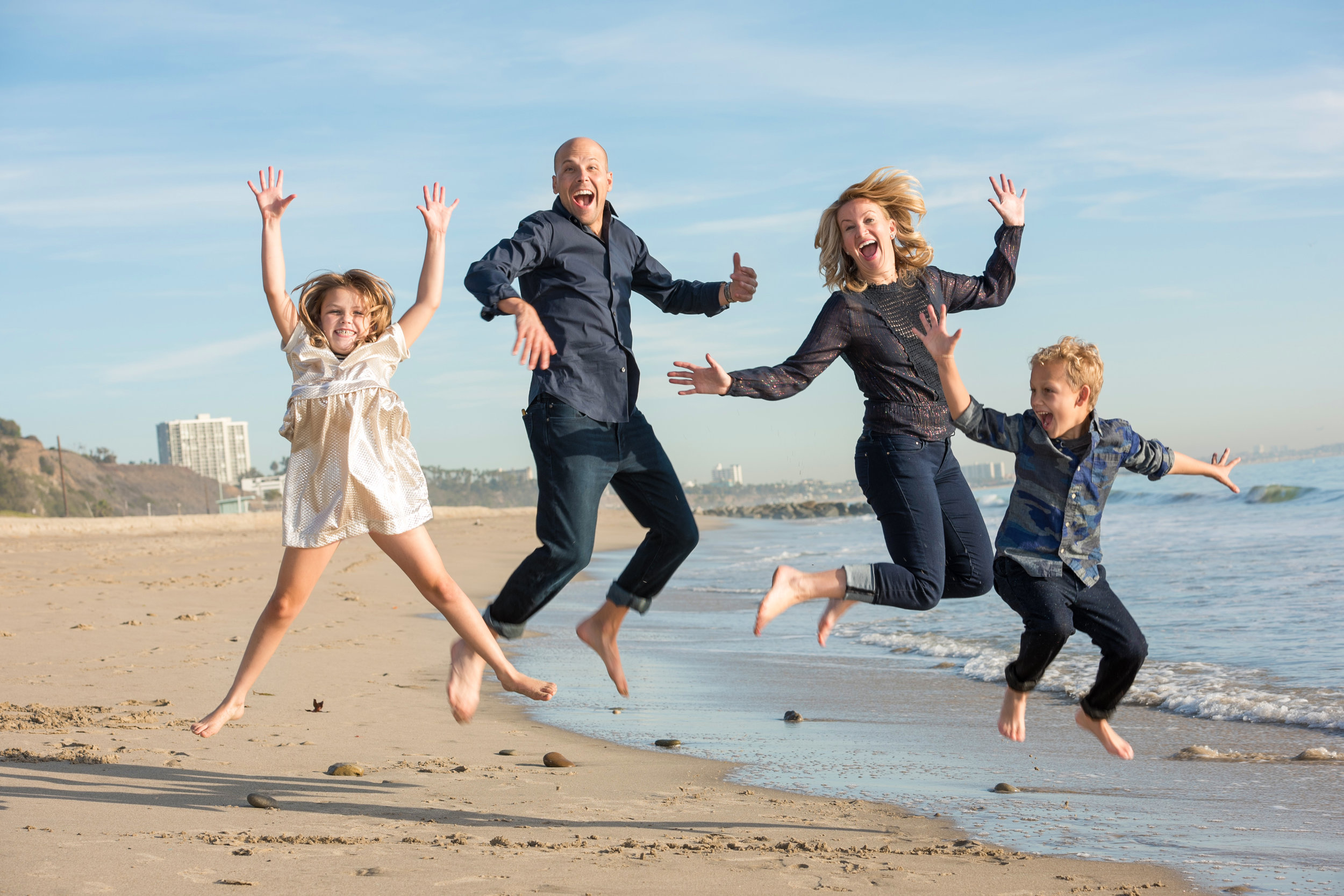 Family of four jumping at the beach