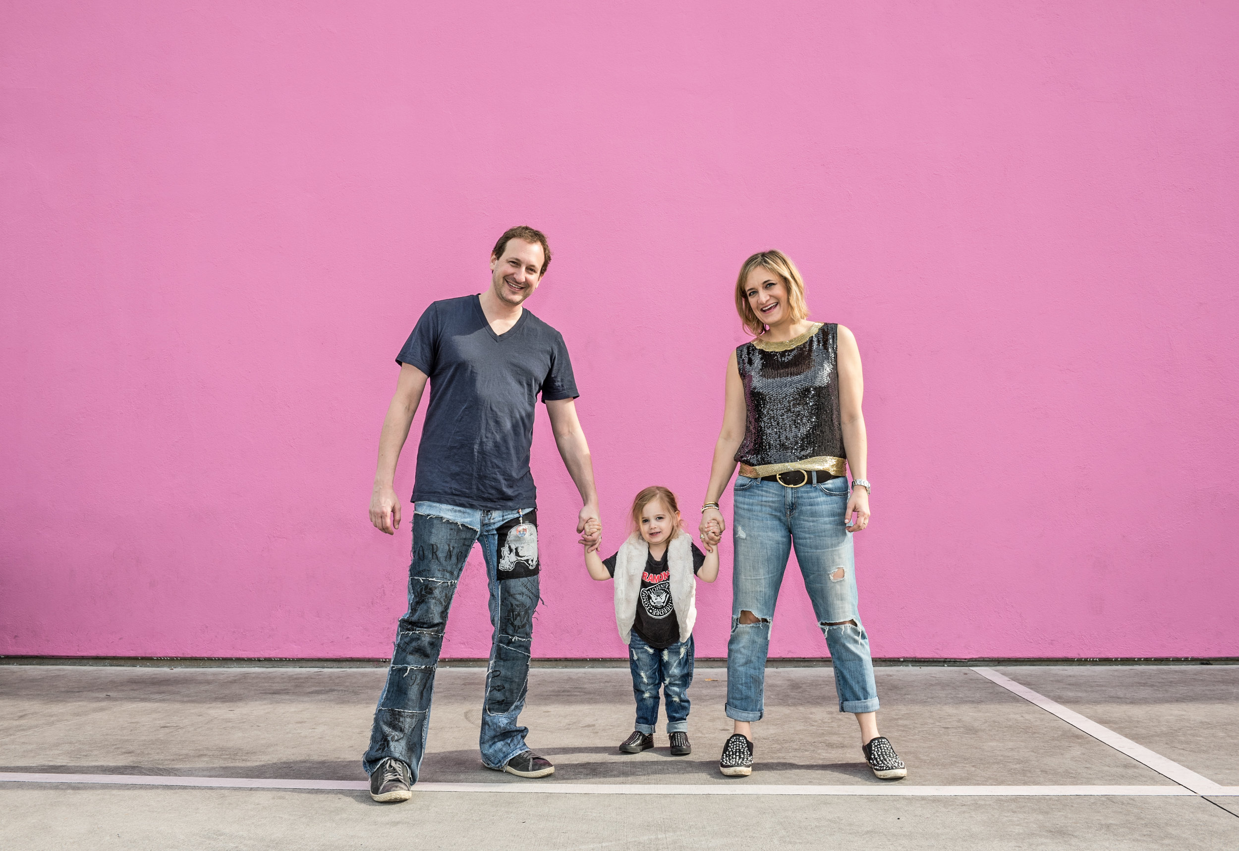 Family of three holding hands all wearing torn jeans