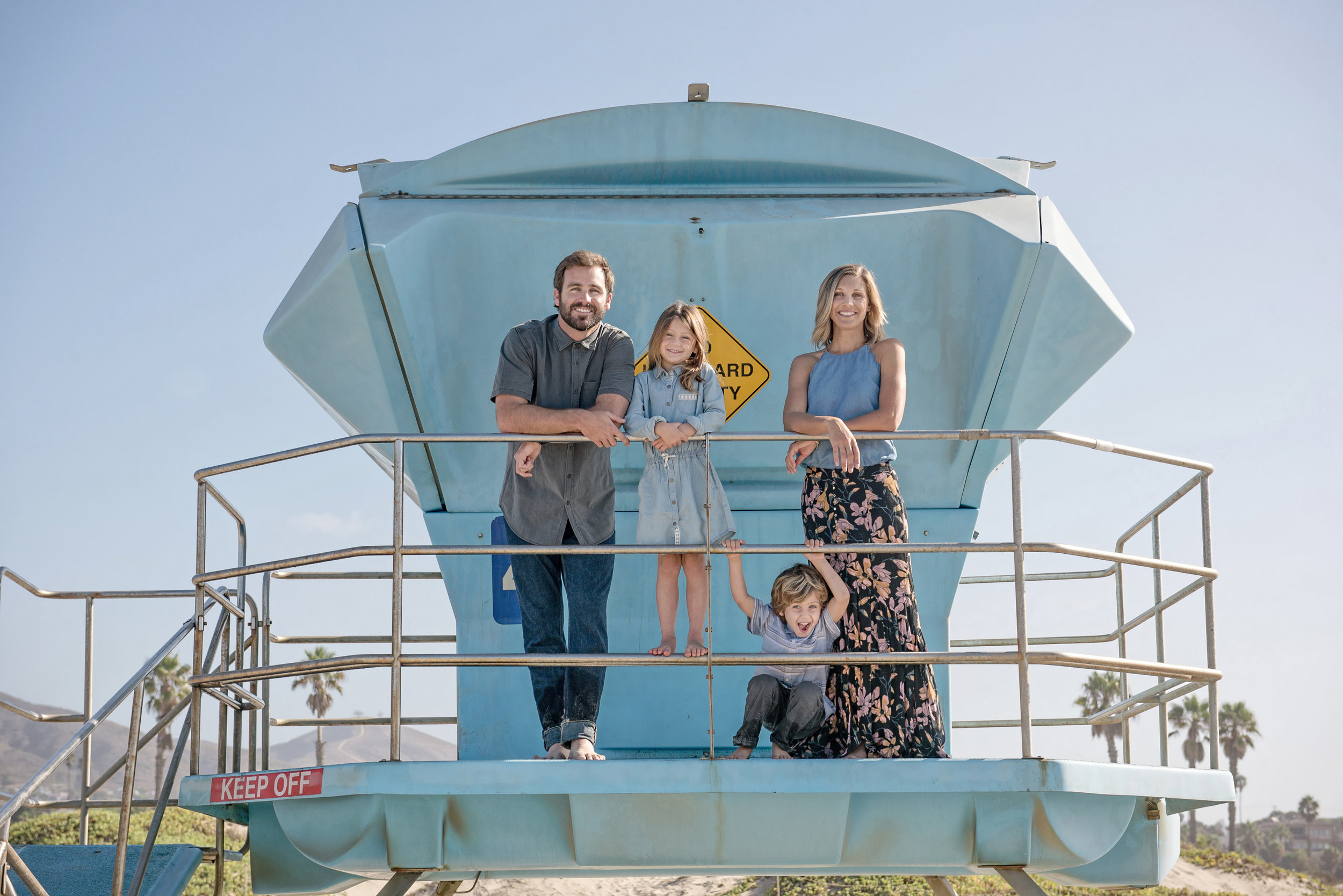 Family of three looking down from a life guard tower