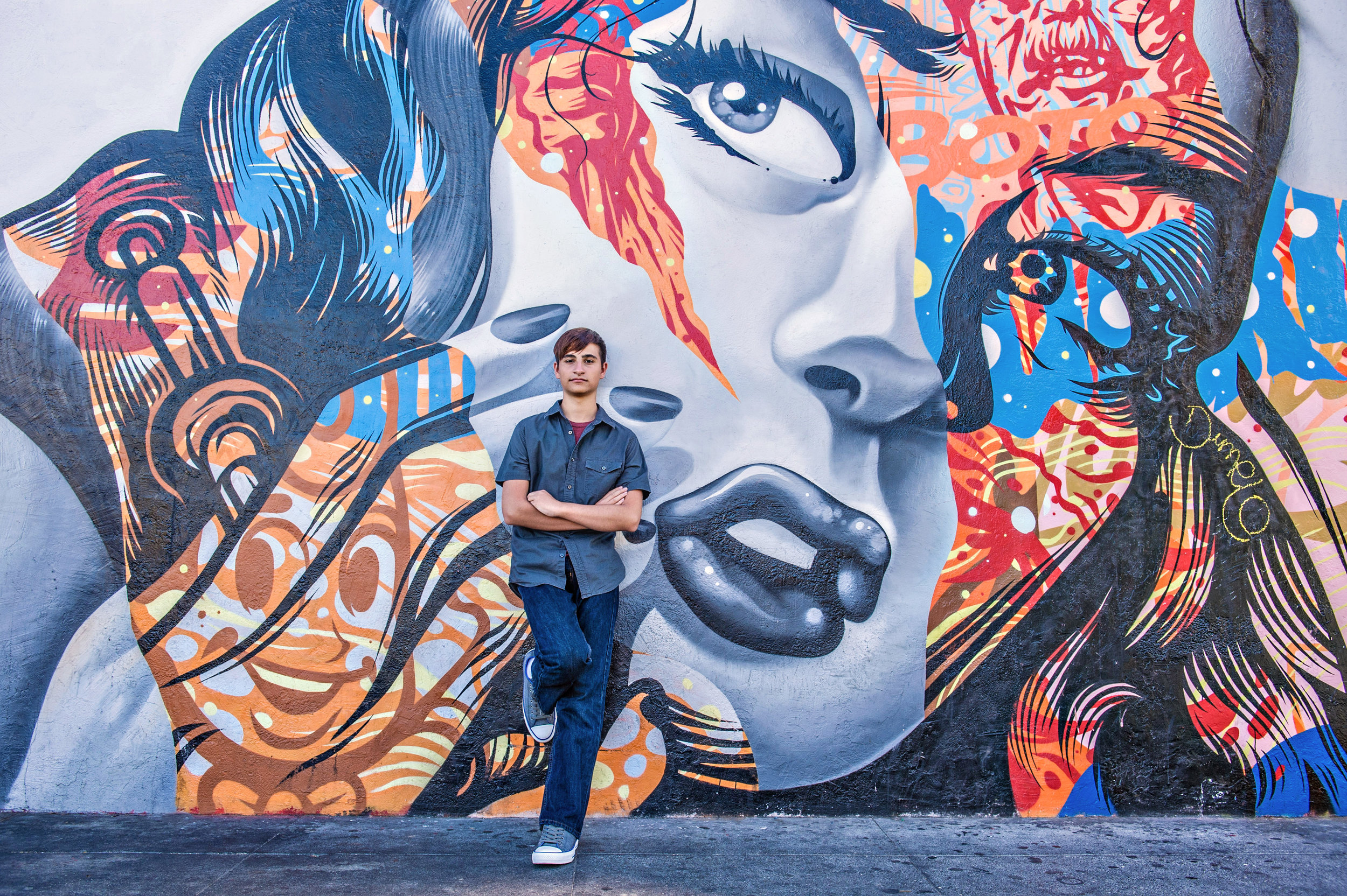Young man leaning against a wall with an artist's depiction of a woman