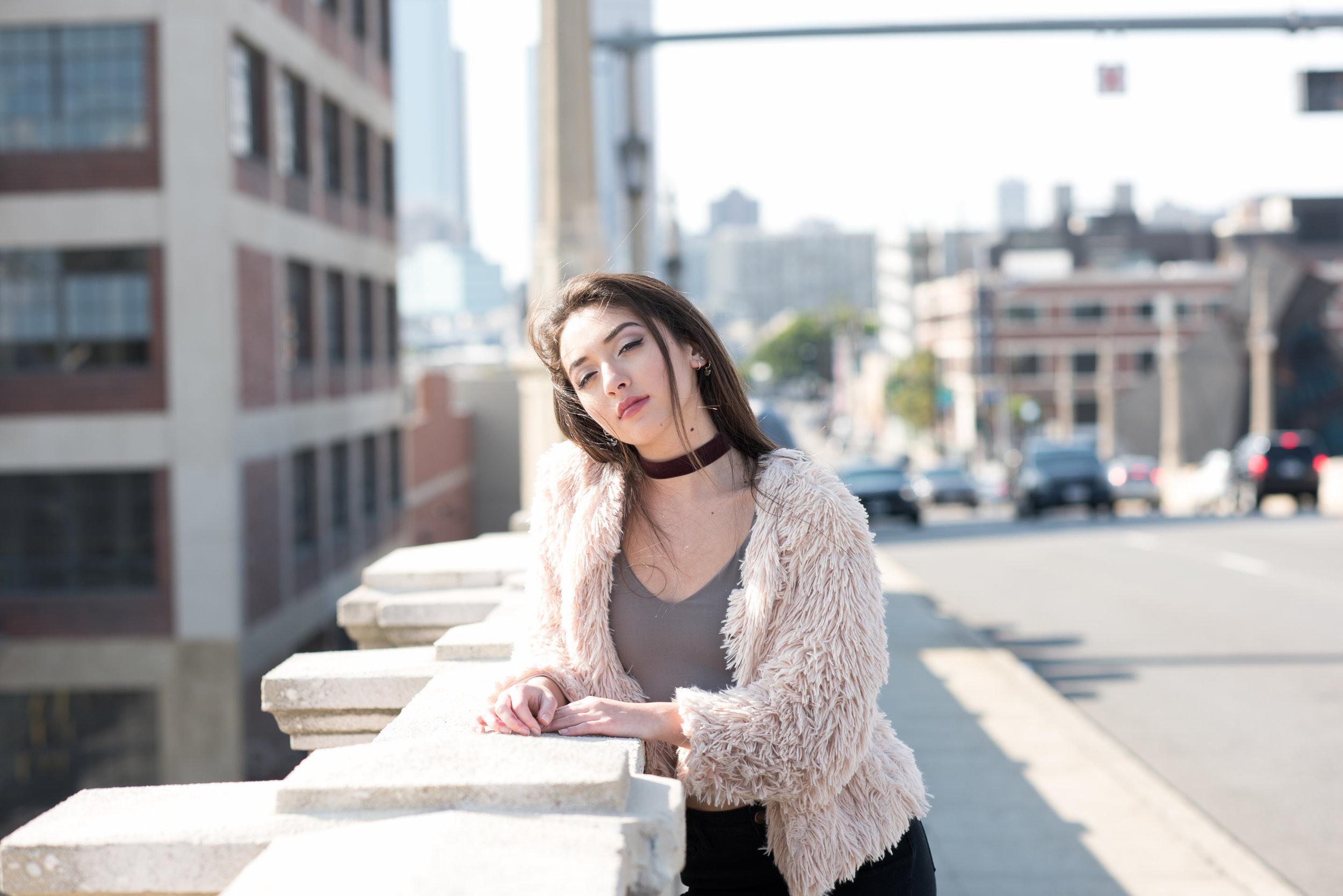 Senior girl wearing a fur coat leaning against bridge railing
