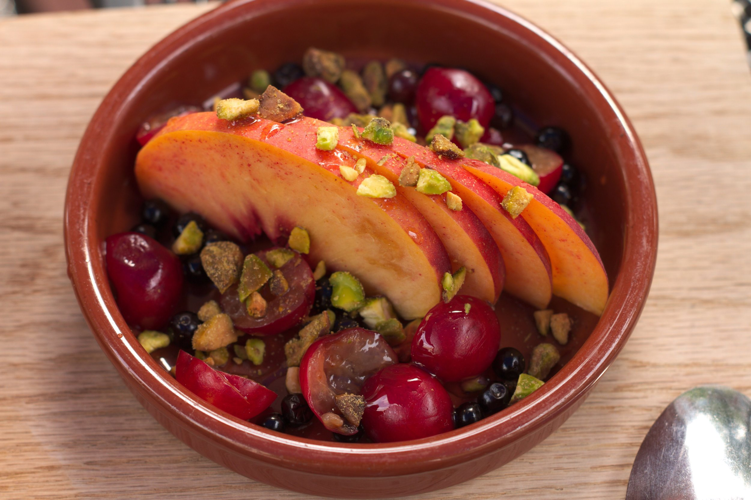 Sliced peaches with pistachios and sour cherries.