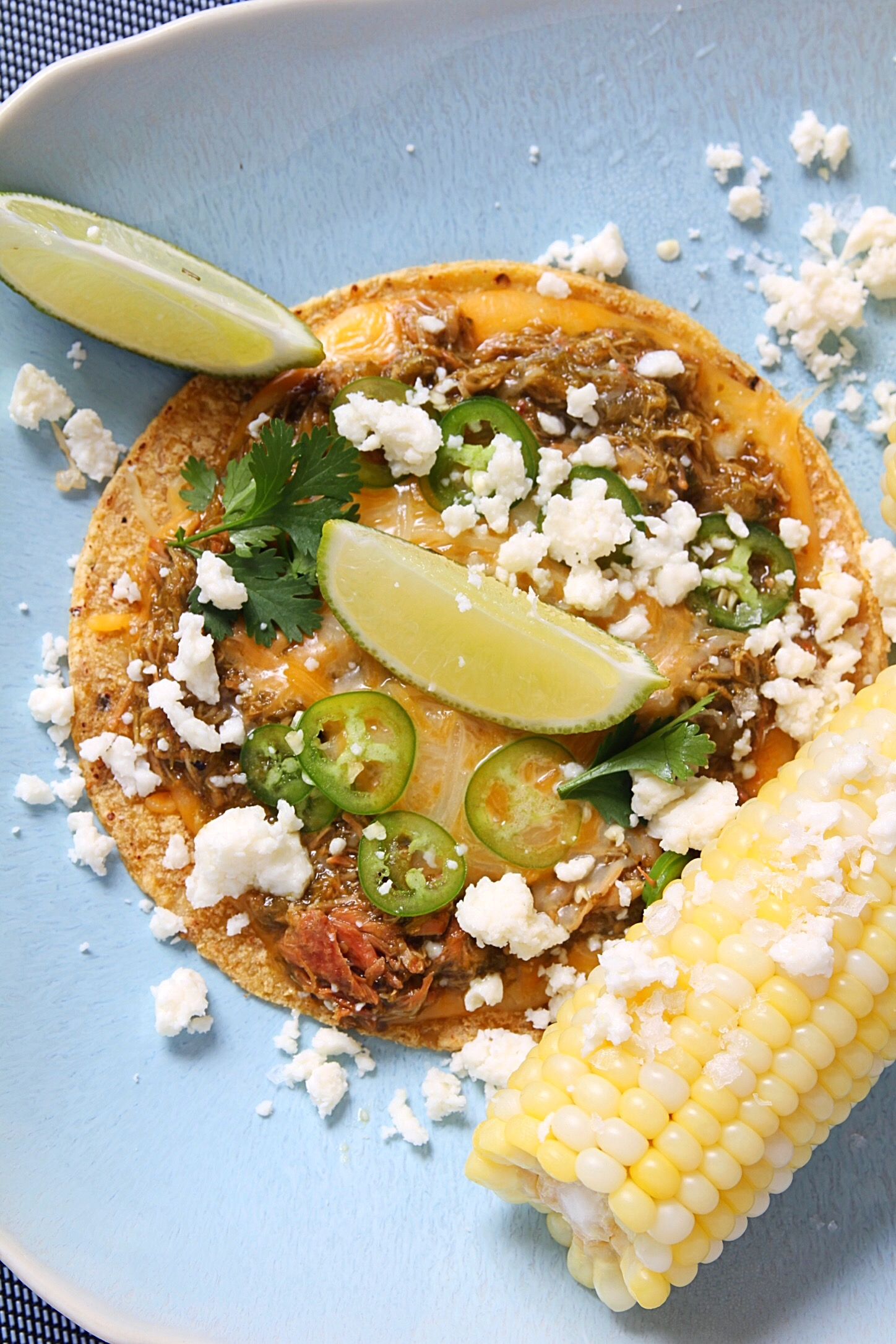 Chicken chili verde taco with Serrano peppers, extra cheese, and corn on the cob