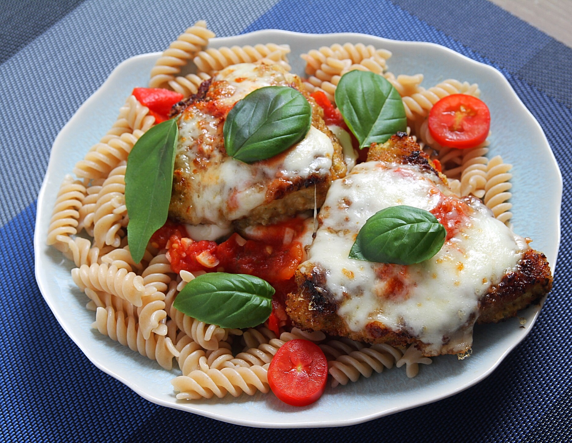 Chicken Parmesan with homemade tomato sauce and fresh basil. GF pasta underneath.