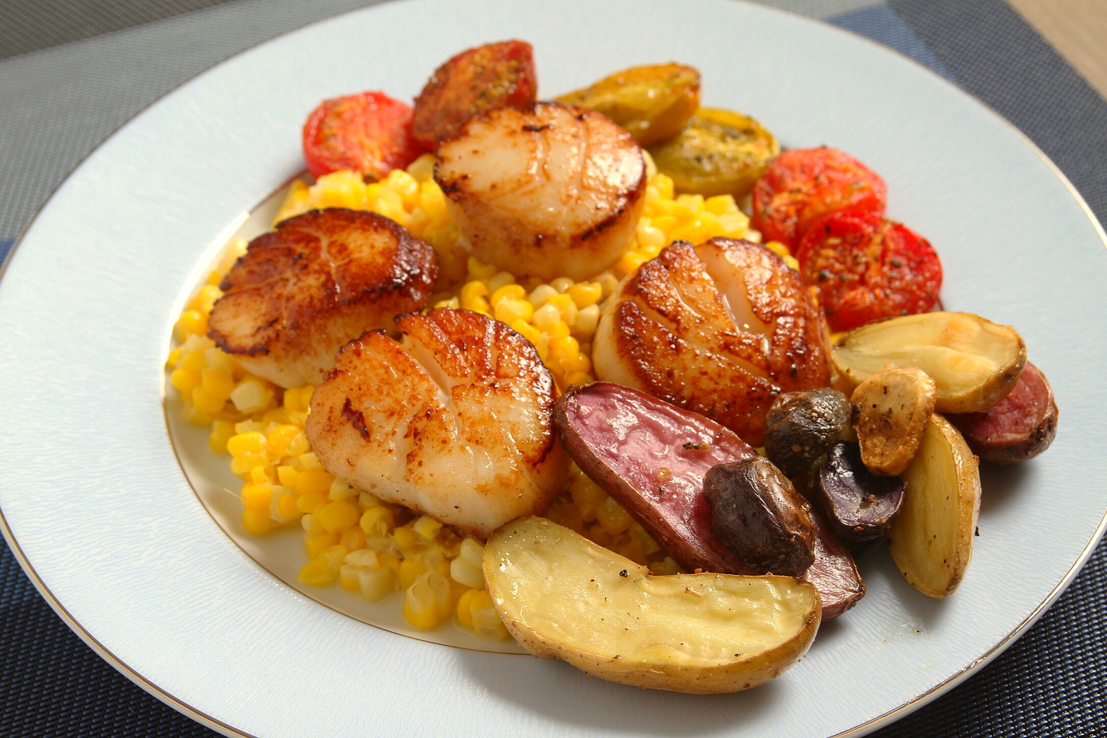 Seared scallops with fingerling potatoes, corn, and roasted tomatoes.