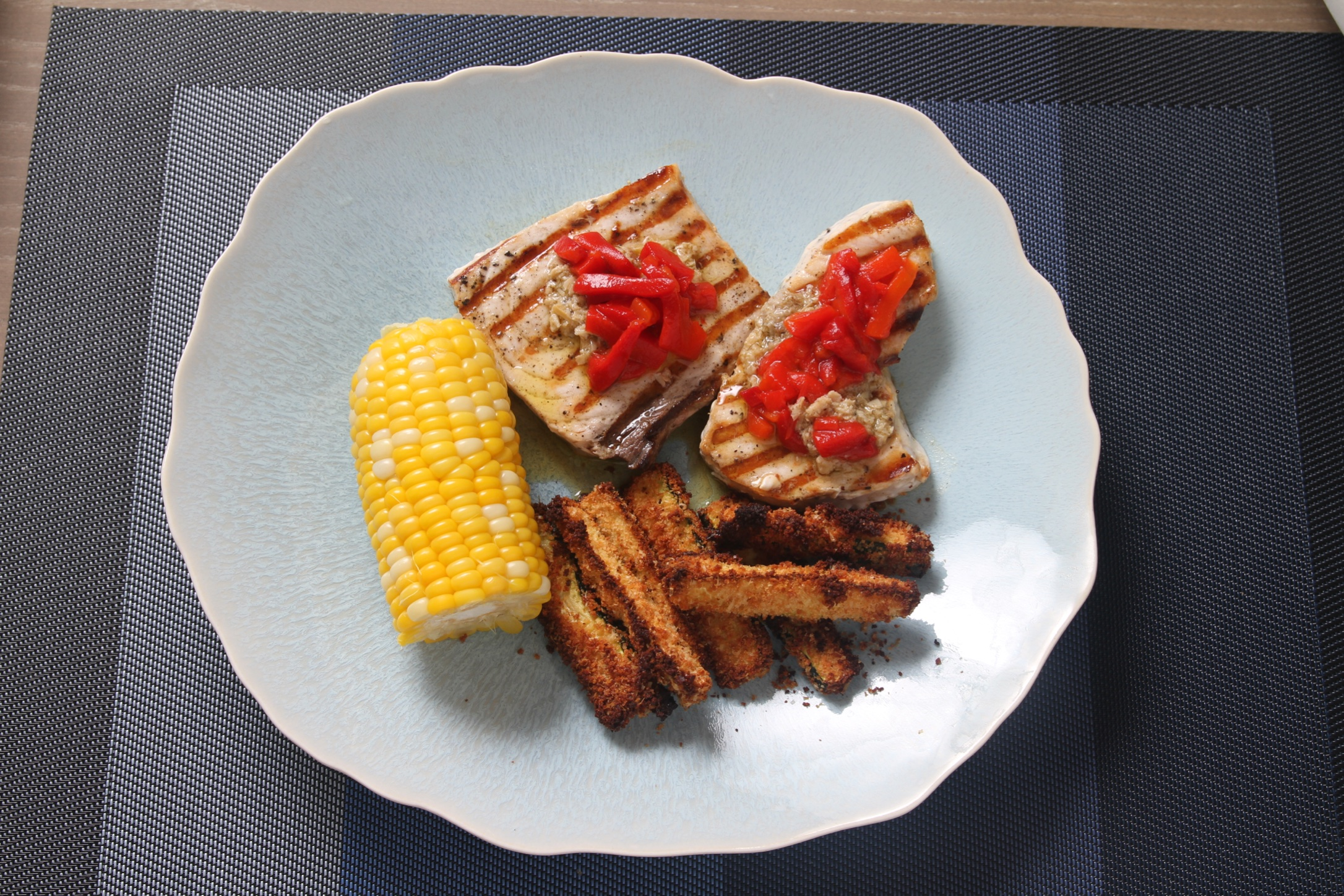 Pan-grilled swordfish with baked zucchini sticks and corn-on-the-cob.