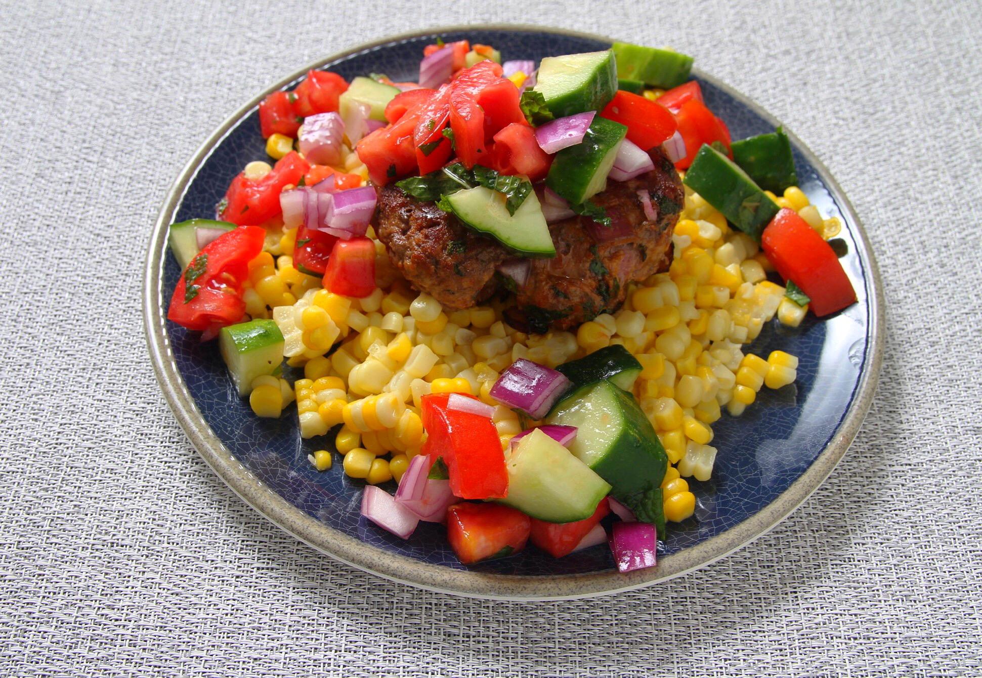 Lamb burger with Greek salad and sweet corn.