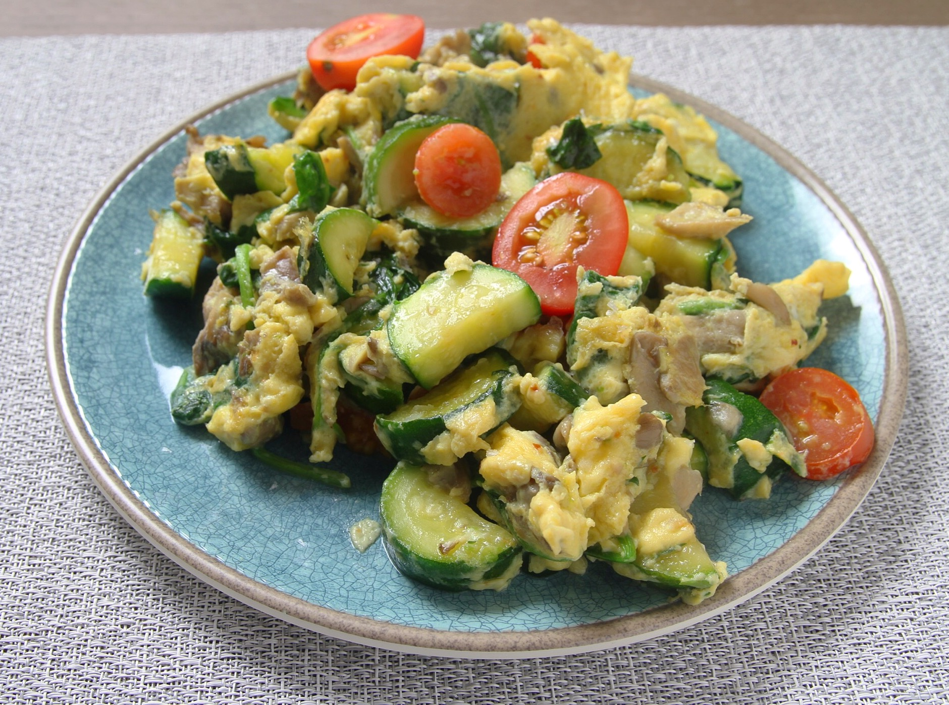 Scrambled eggs with zucchini, mushrooms, spinach, and tomatoes.