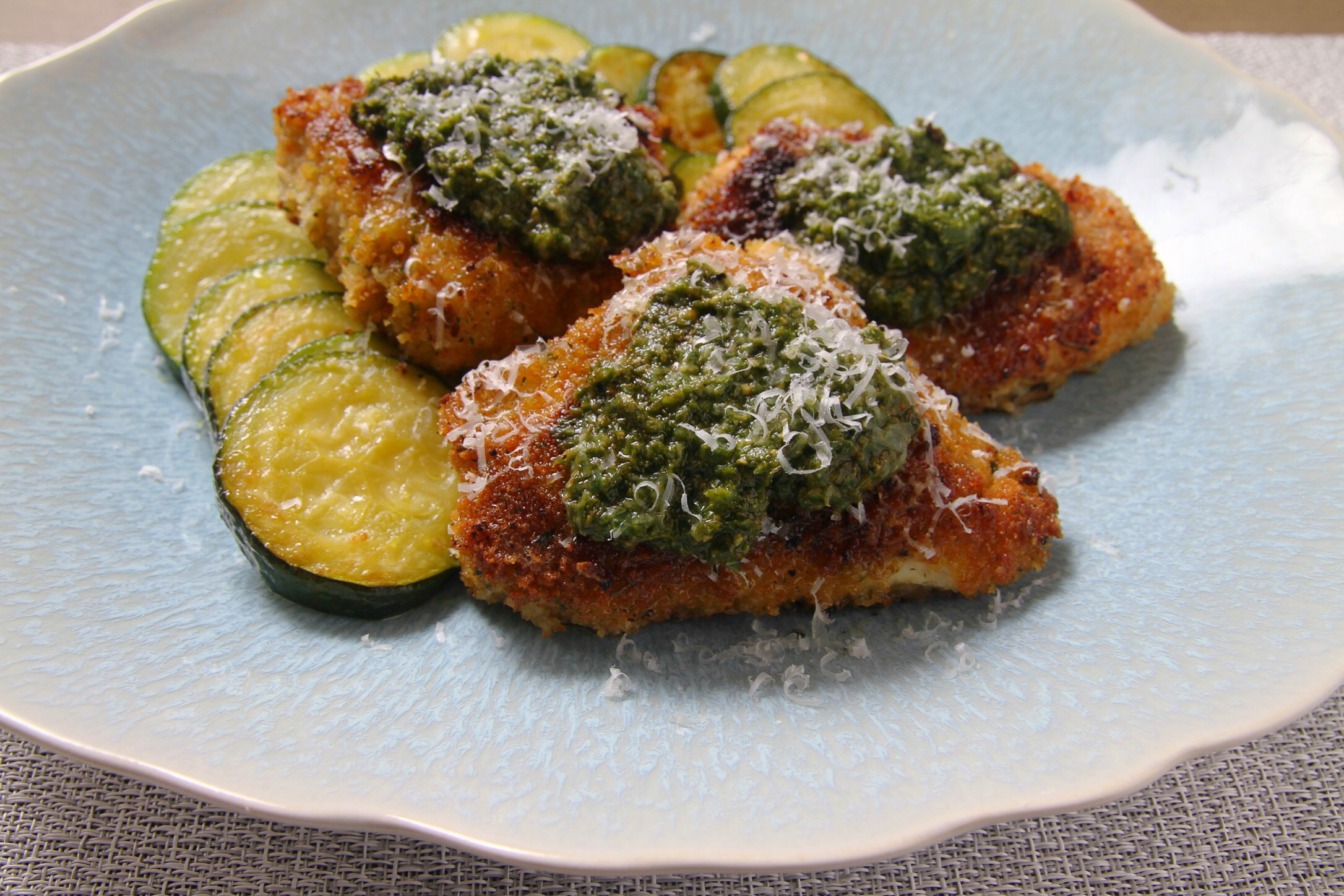 Italian breadcrumb chicken topped with basil pesto and a side of sauteed zucchini.