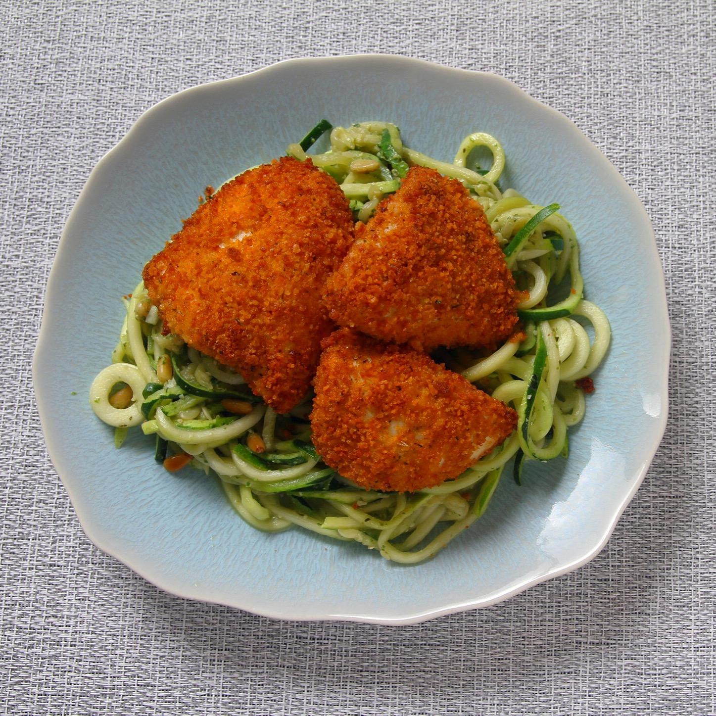 Crispy spicy oven baked chicken with pesto zucchini noodles.