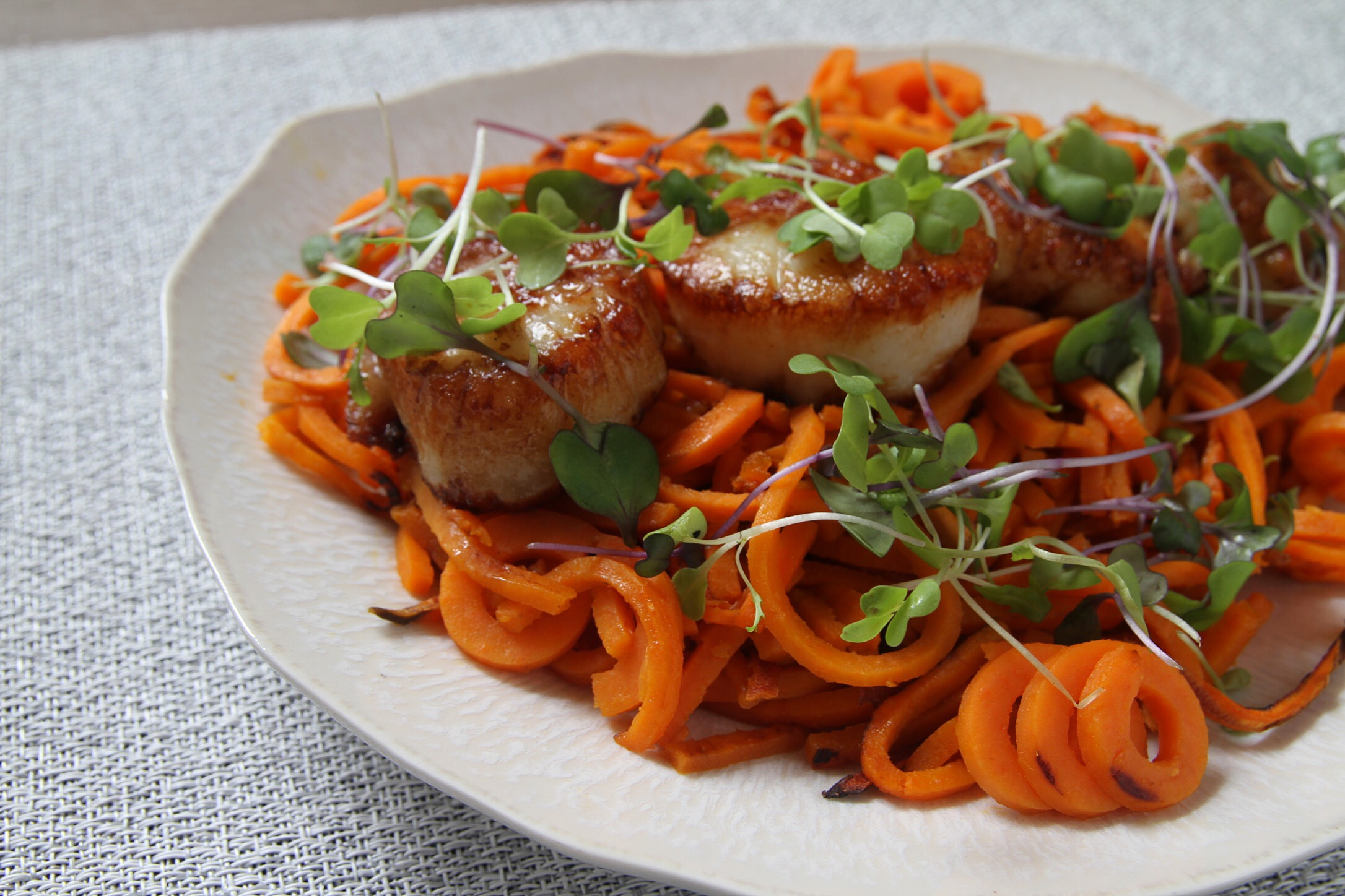 Seared sea scallops over sweet potato noodles, topped with local micro greens.