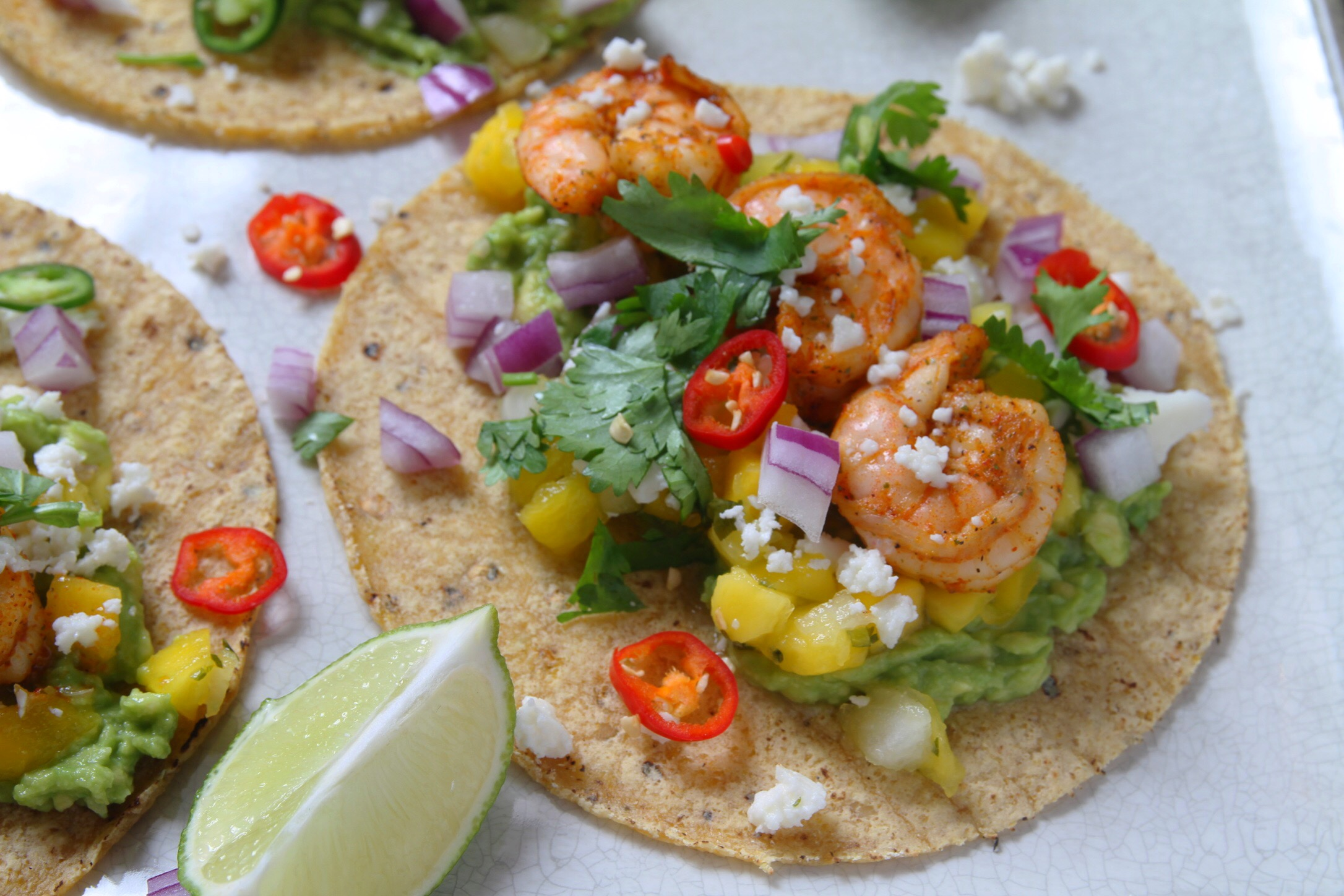 Cajun shrimp tacos with mango salsa, guacamole, hot peppers, red onion, and queso fresco. Plus cilantro! And lime garnish.