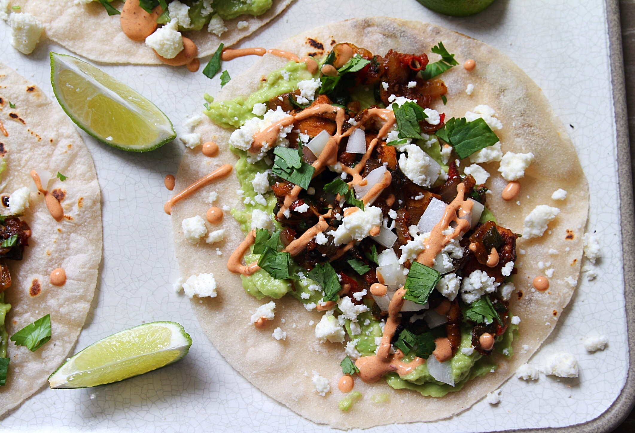 Spicy chicken tacos with guacamole and queso fresco. Lime wedge garnish.