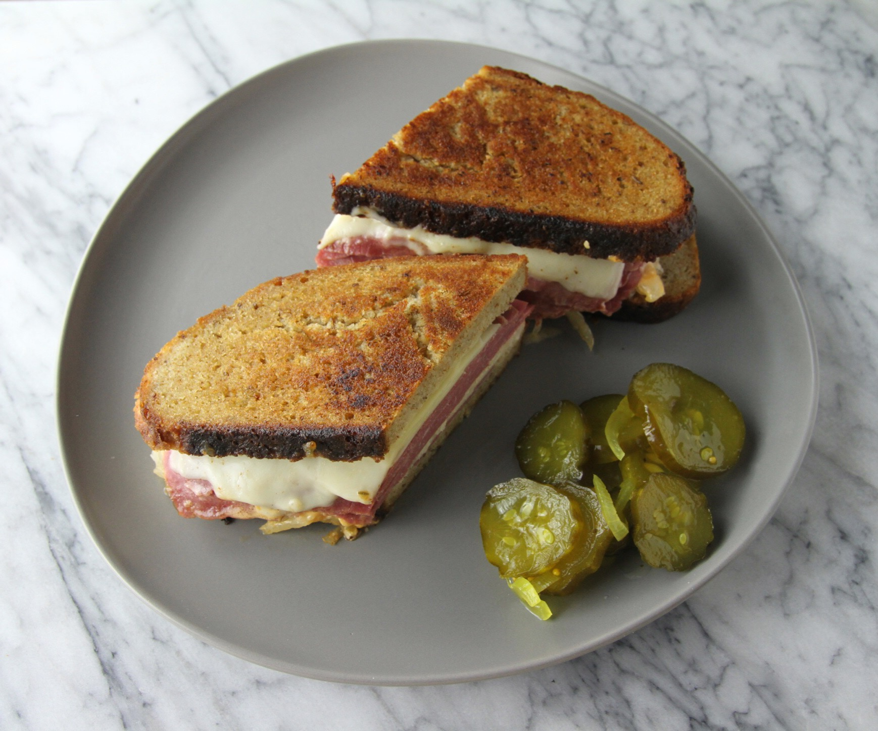 Reuben with a side of homemade pickles.