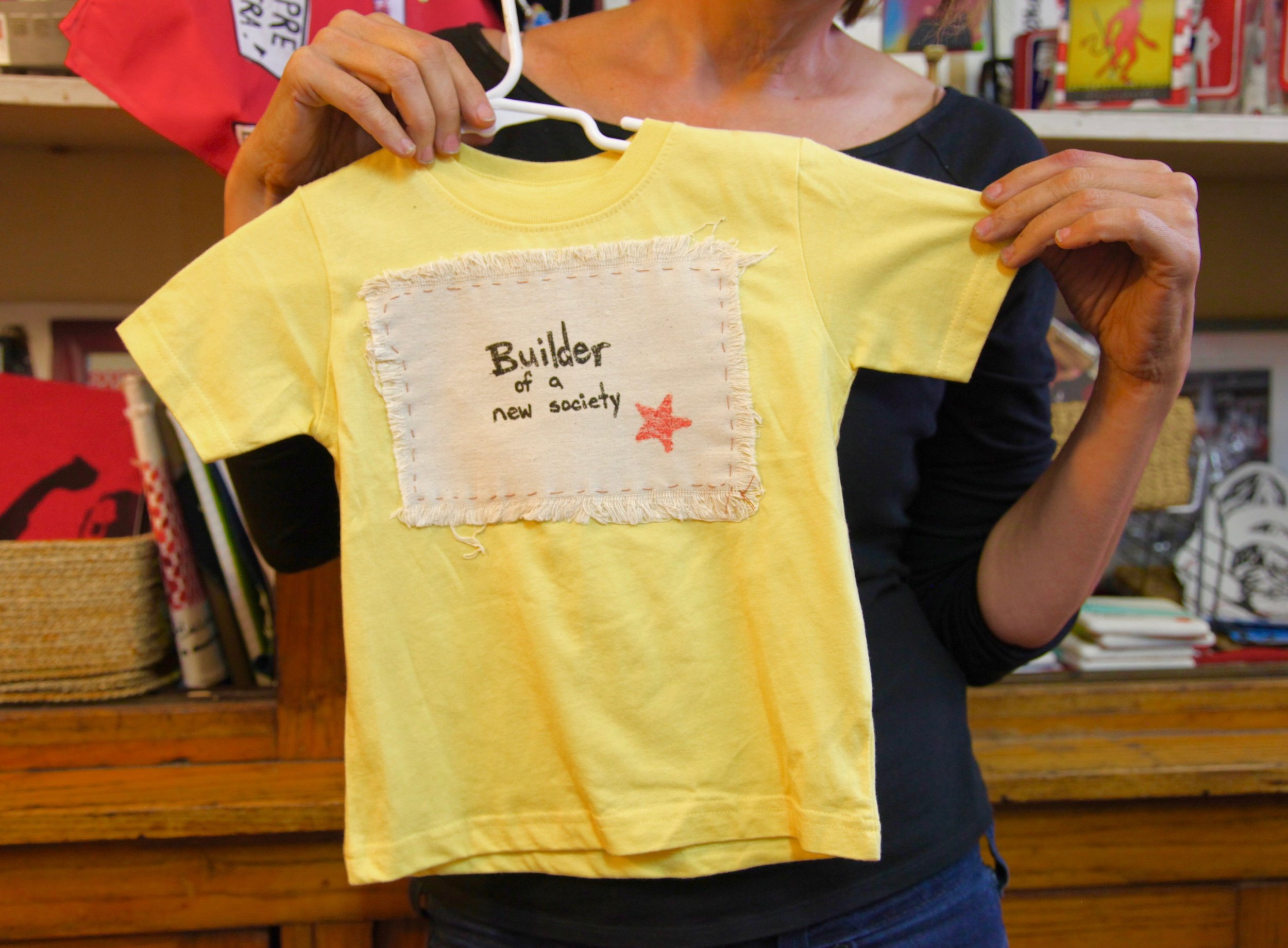 """""""The whole store really looks forward and positive … That's one of the reasons you're seeing a lot of baby clothes. Babies are the future."""" Stephanie noticed that many people are wary of politicizing children. But she sees it as a """"playful and fun way to share political culture."""" With her array of shirts with slogans like """"Builder of a new society,"""" Stephanie hopes to show her belief that it's possible to raise kids progressively and politically."""