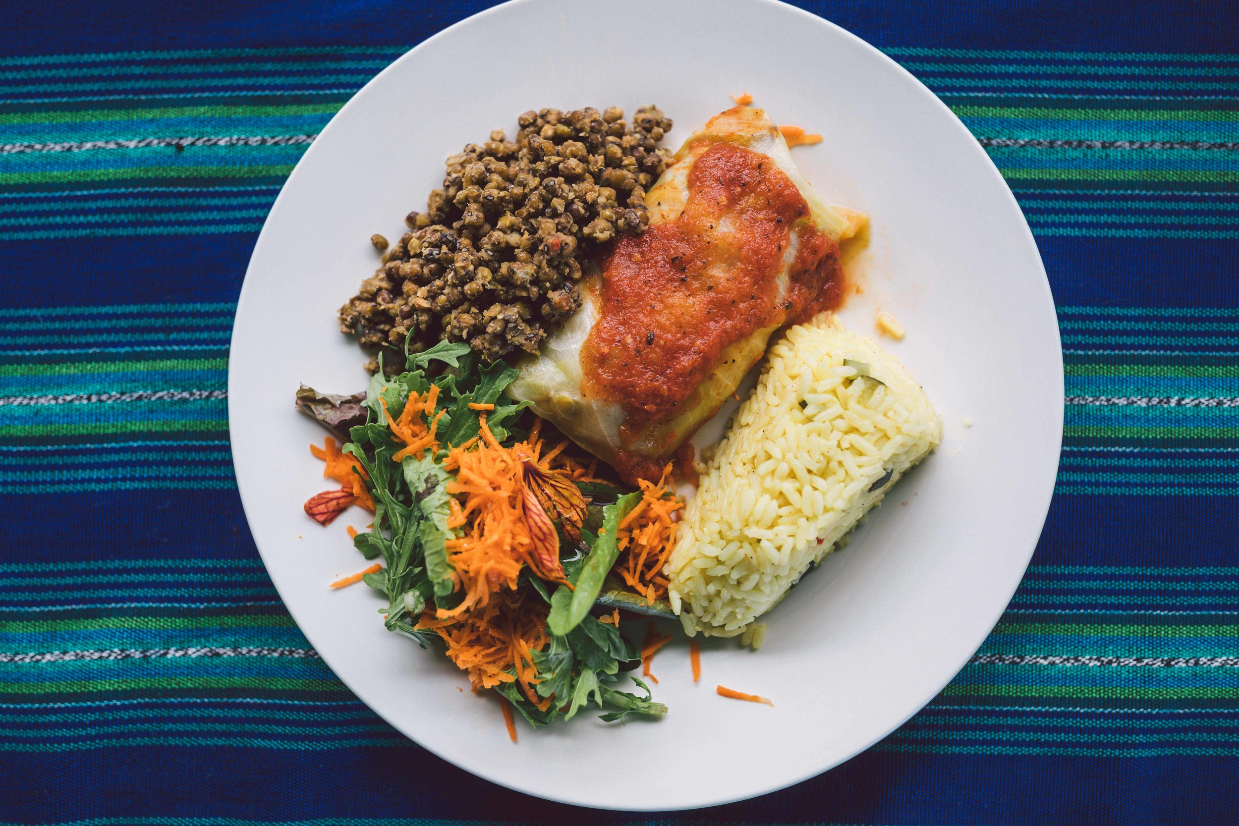 A plate with lentils, green salad, rice, and a burrito covered in tomato sauce. Fresh, healthy food served during the Discovering Birth Midwifery Retreat, at the Bambu Guest House, Lake Atitlan, Guatemala, July 14-27, 2019